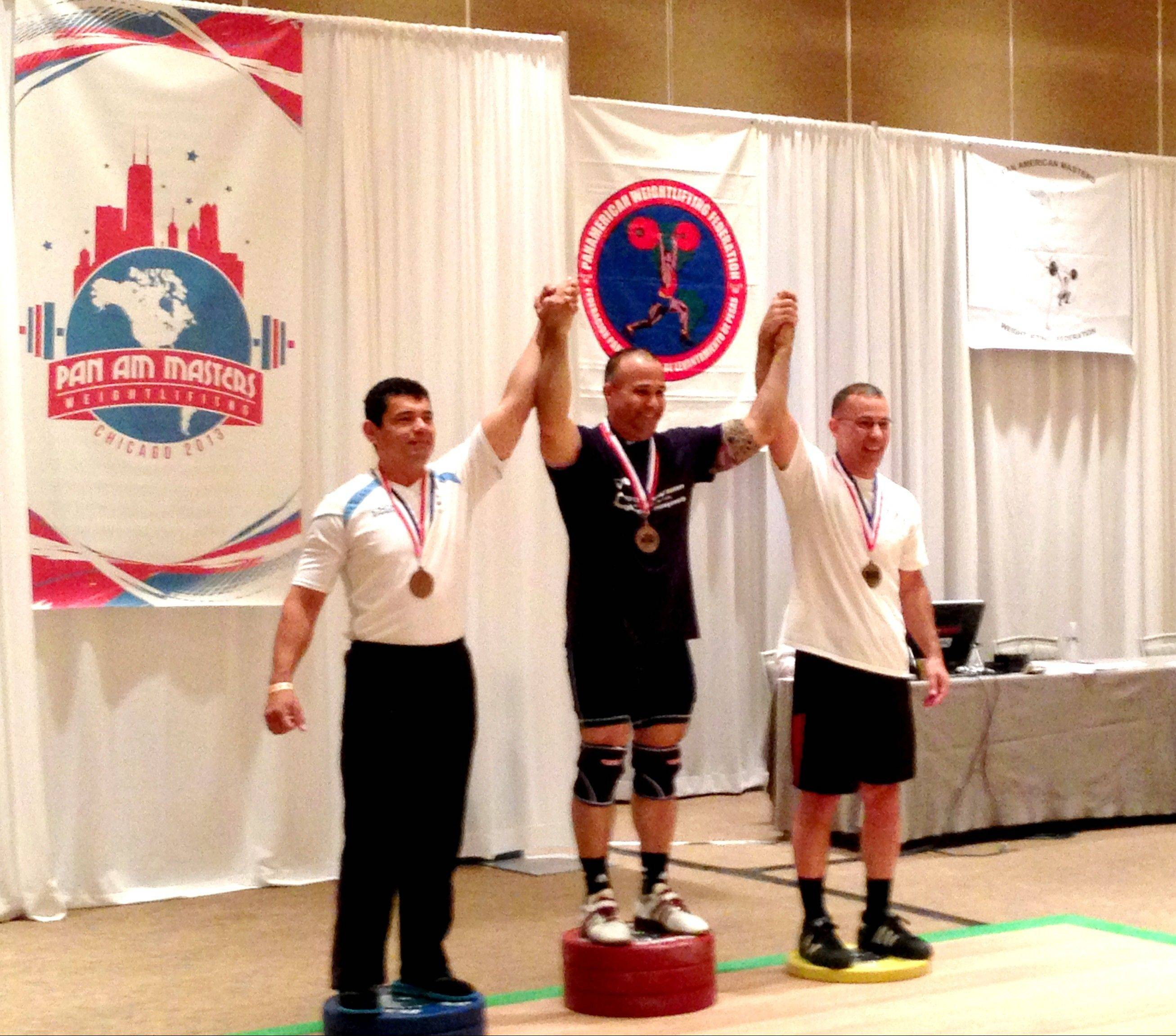 American Robert Arroyo, center, set three records at the 2013 PanAm Masters Weightlifting Championships Sunday morning. Joining him on the podium were Jose Reyes, left, and Jeff Tincher, right.