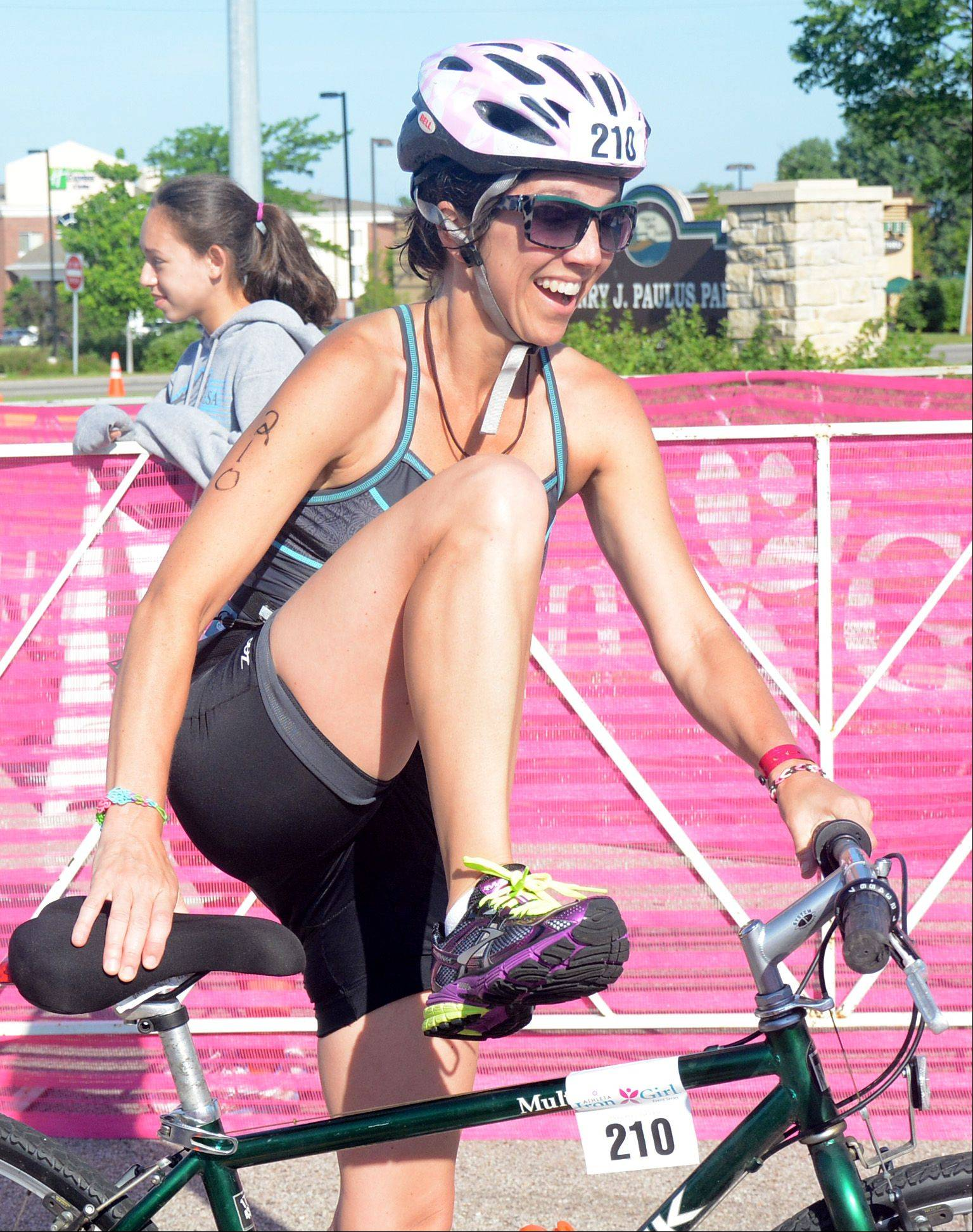 Cindarae Malin, of Lake Zurich, dismounts her bike during the Athleta Iron Girl Triathlon in Lake Zurich Sunday.