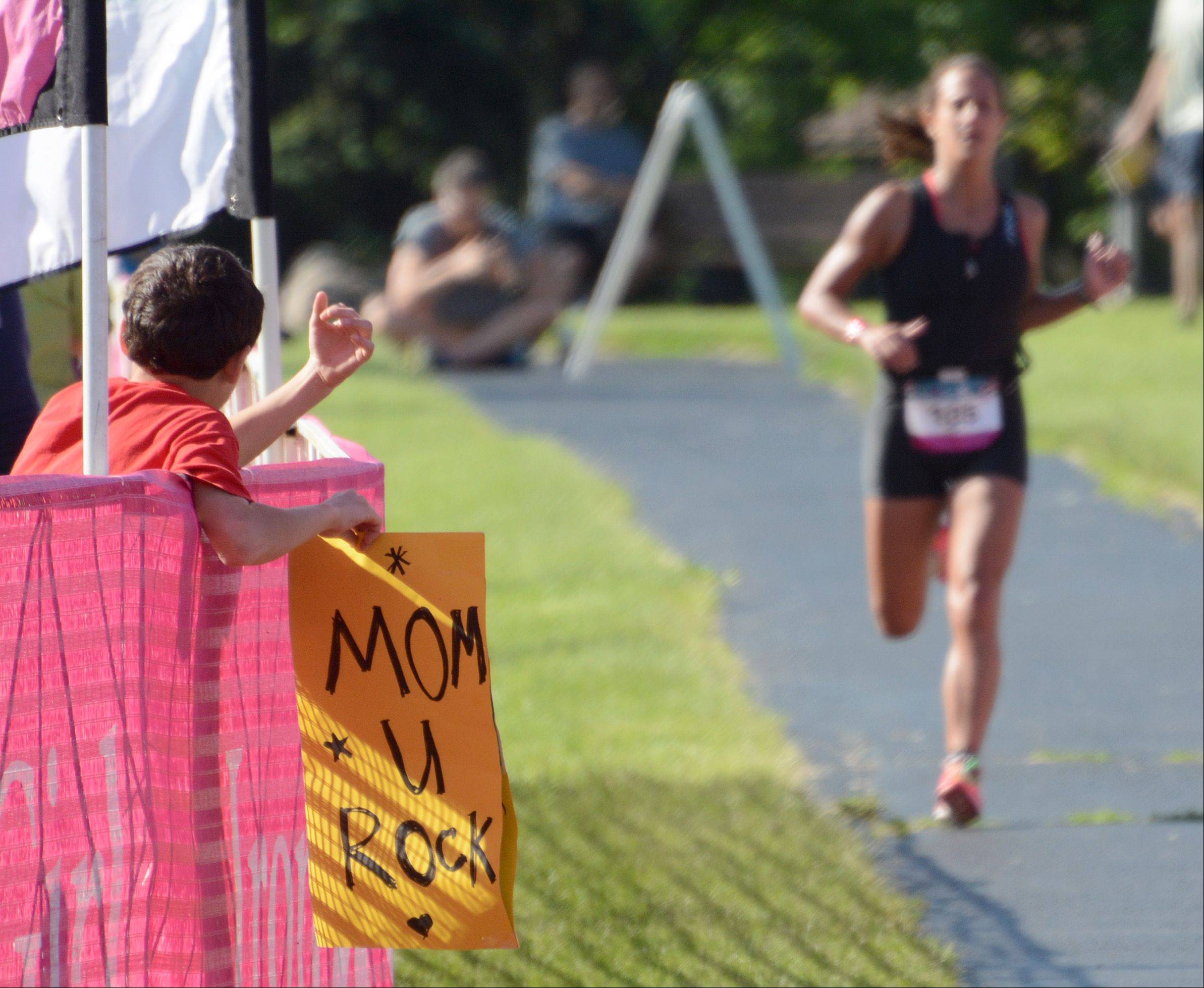 A child holds an inspirational sign for his mother during the Athleta Iron Girl Triathlon in Lake Zurich Sunday.