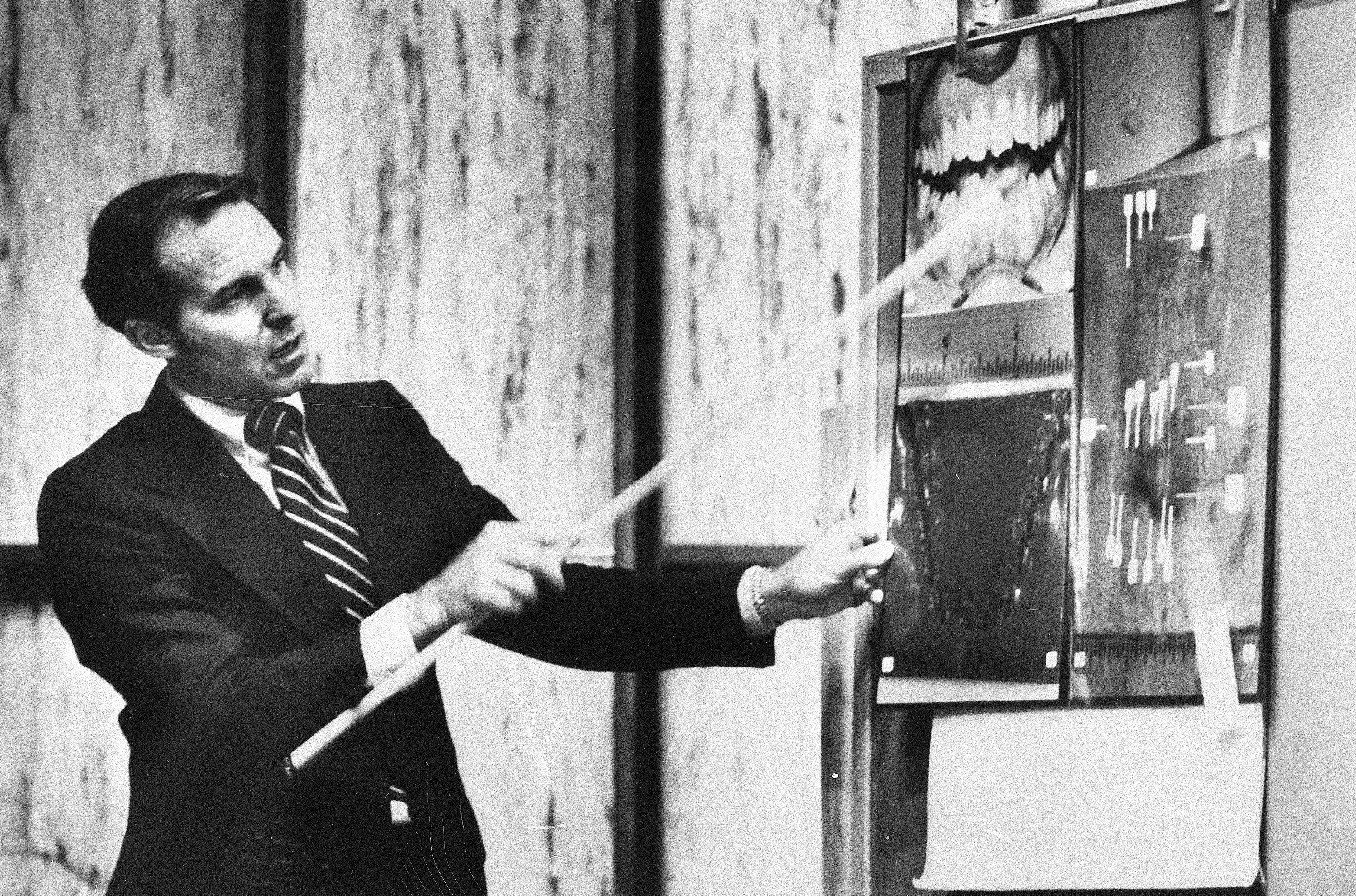 Forensic odontologist Richard Souviron pointsg to a blown-up photograph of Theodore Bundy's teeth during Bundy's murder trial in Miami, Fla. Souviron, one of the prosecution's key witnesses, showed the jury that only Bundy's teeth could have made the bite marks discovered on one of the slain coeds in the Chi Omega murder case.