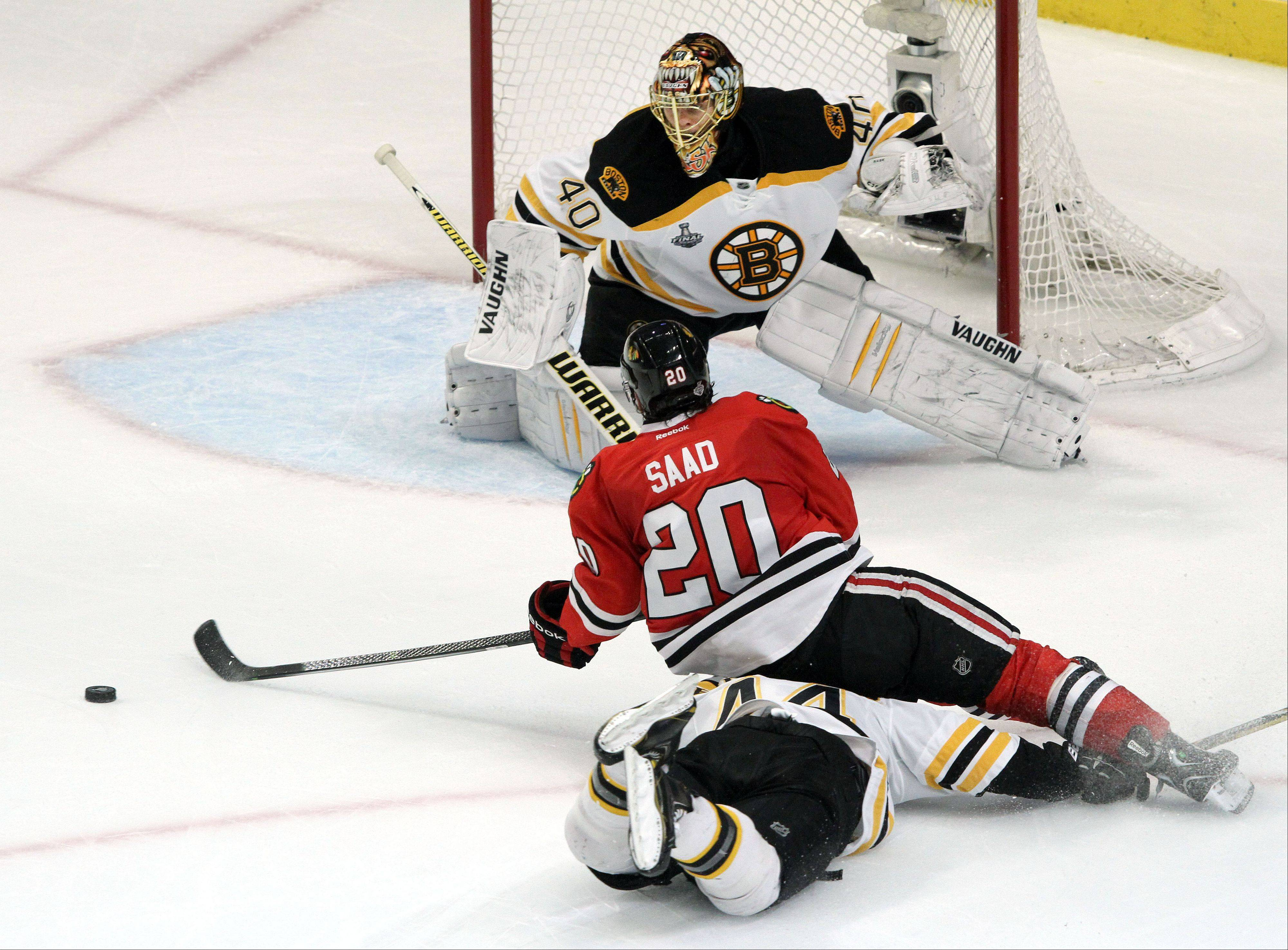 The Blackhawks' Brandon Saad gets tripped by Bruins defenseman Dennis Seidenberg during Game 2 of the Stanley Cup Final at the United Center on Saturday.