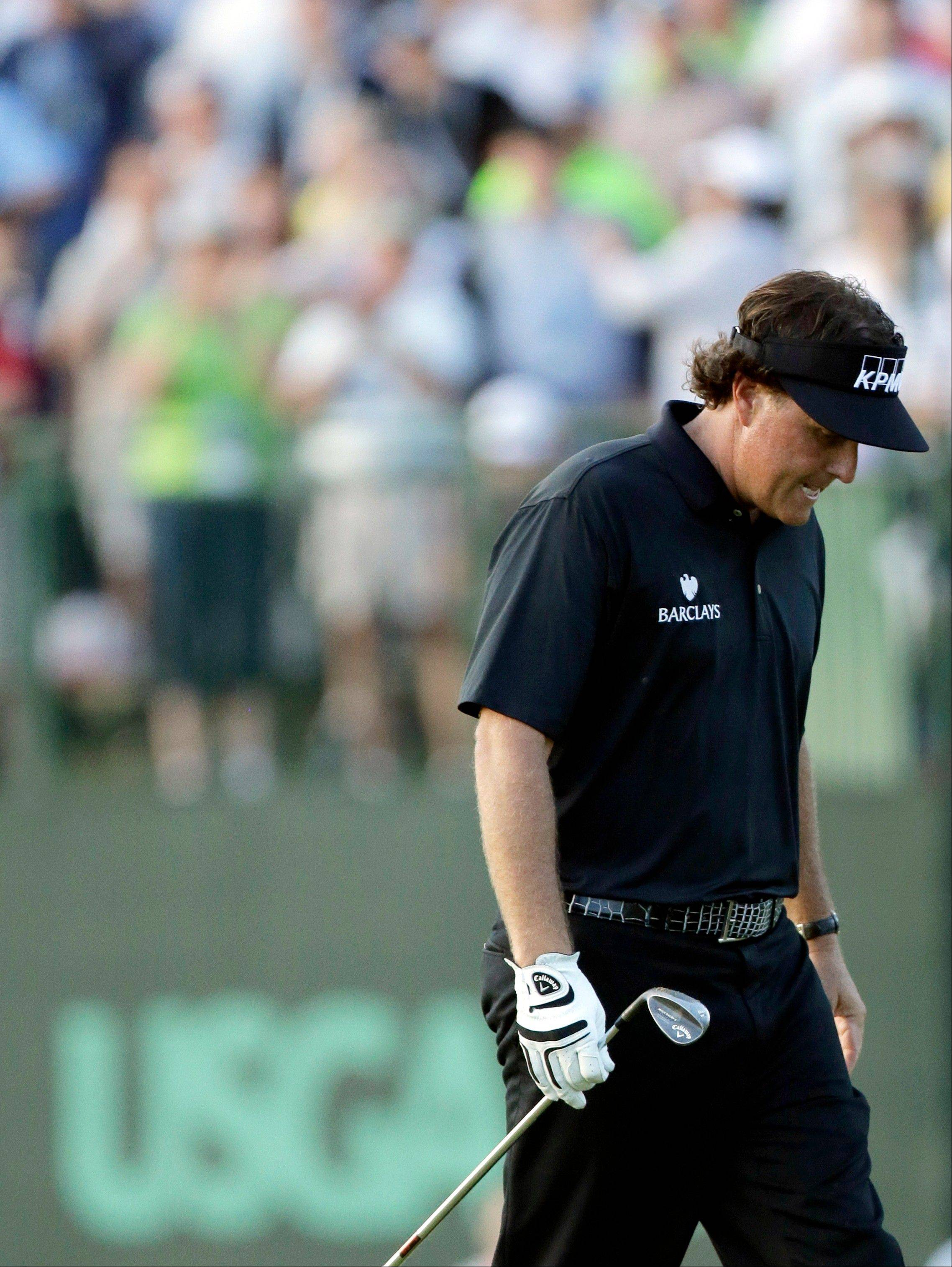 Phil Mickelson reacts after missing a shot on the 18th hole during the fourth round of the U.S. Open golf tournament at Merion Golf Club, Sunday, June 16, 2013, in Ardmore, Pa.
