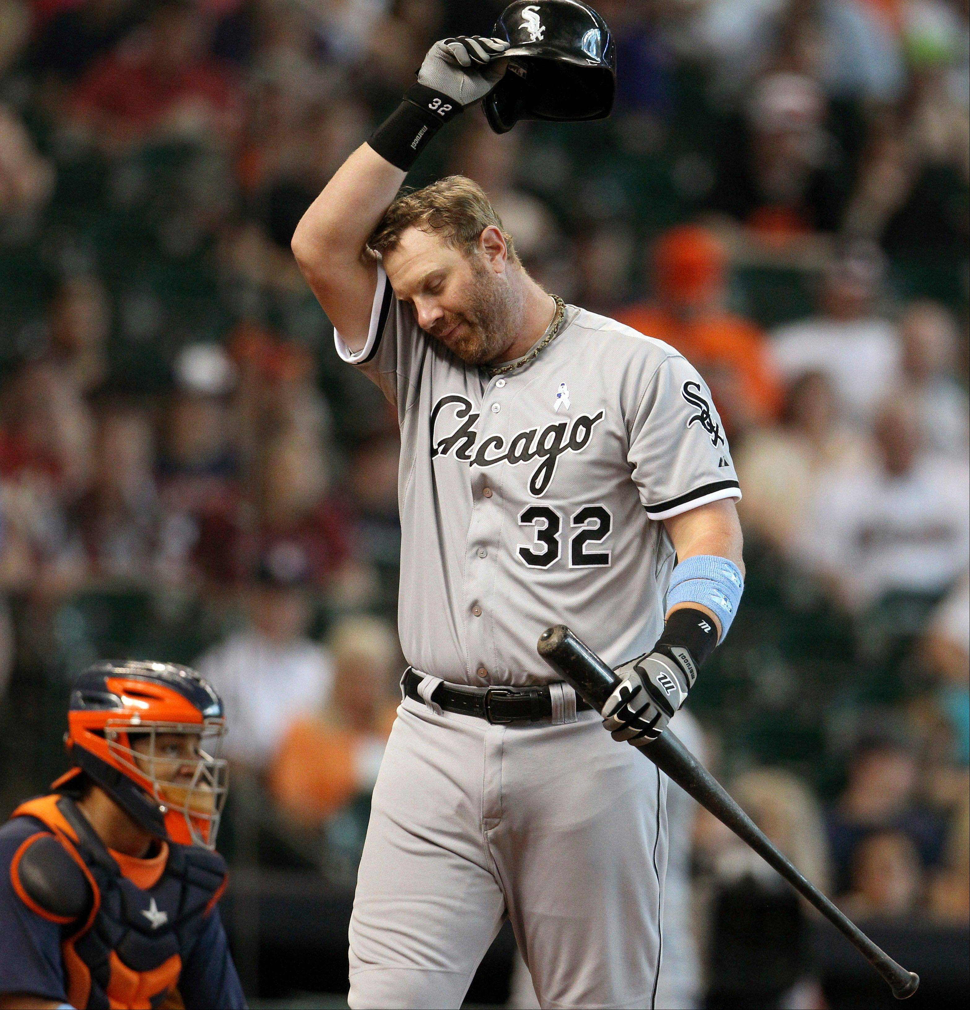 White Sox first baseman Adam Dunn wipes his face while at bat against the Houston Astros during the second inning of a baseball game at Minute Maid Park, Sunday, June 16, 2013, in Houston.