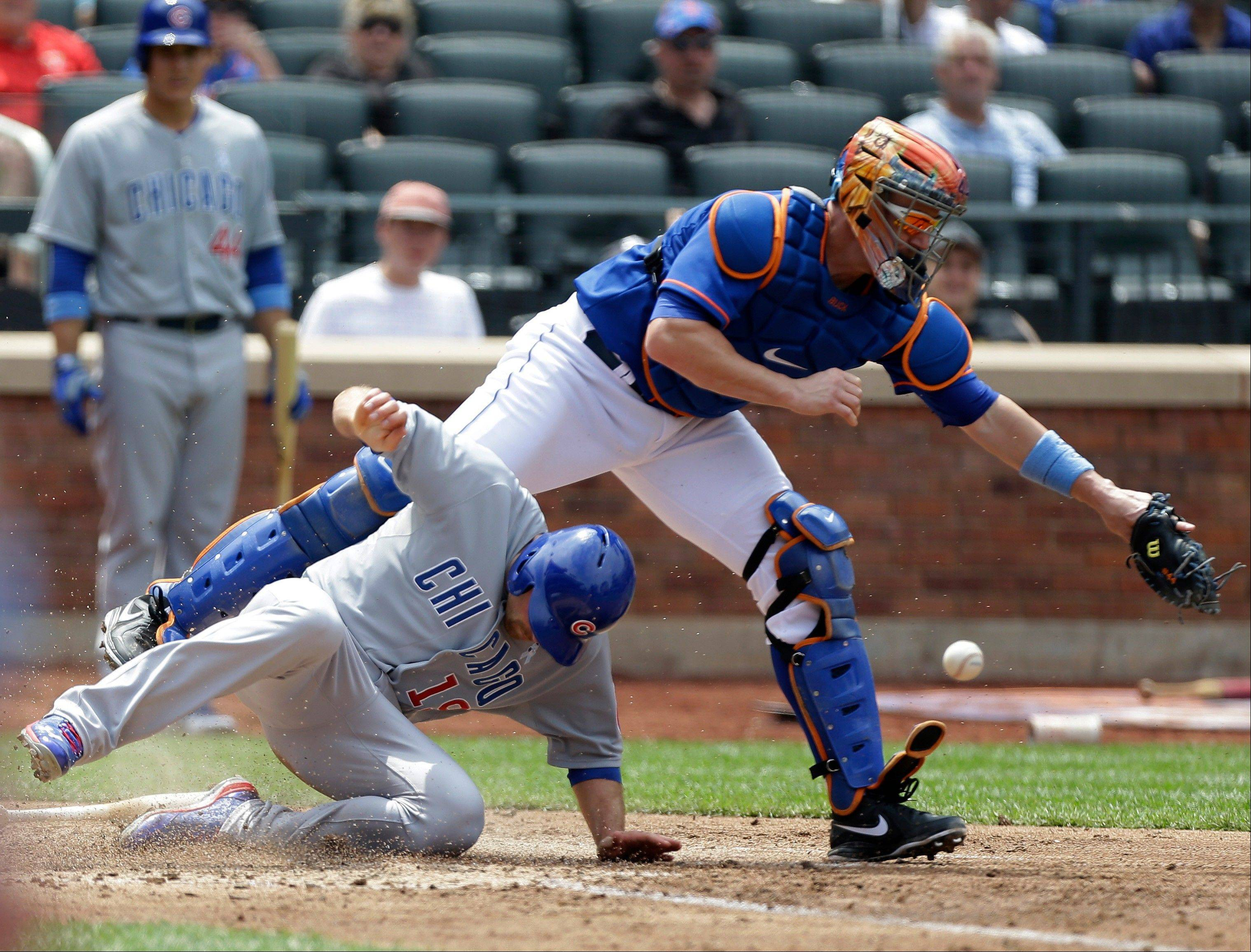 Cubs runner Nate Schierholtz is safe on a Mets throwing error as New York Mets catcher John Buck can't make the play on Alfonso Soriano's fifth-inning, two-run single in Sunday's game in New York.