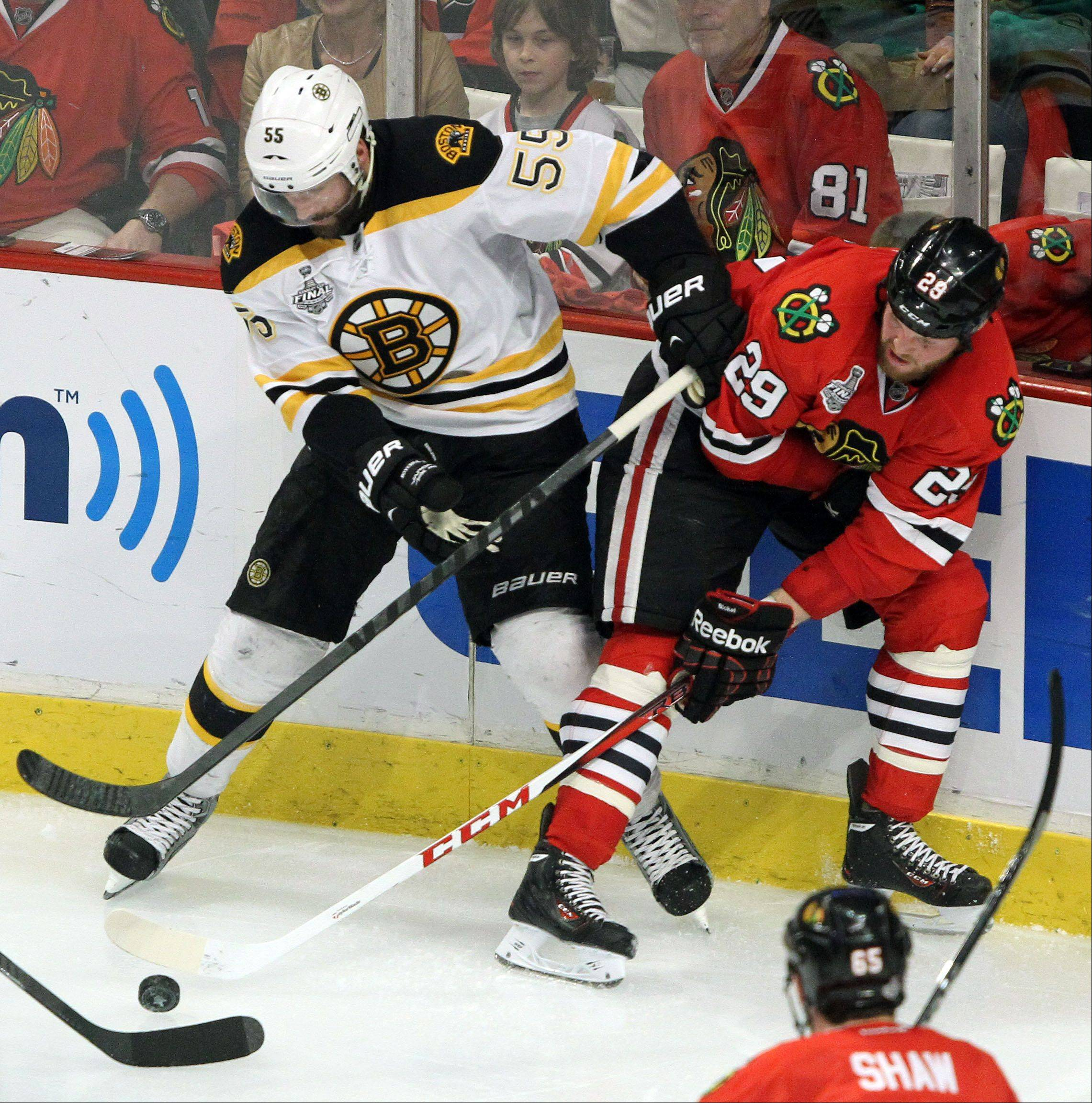 Chicago Blackhawks left wing Bryan Bickell and Boston Bruins defenseman Johnny Boychuk battle during game 2 of the Stanley Cup Finals at the United Center in Chicago Saturday.