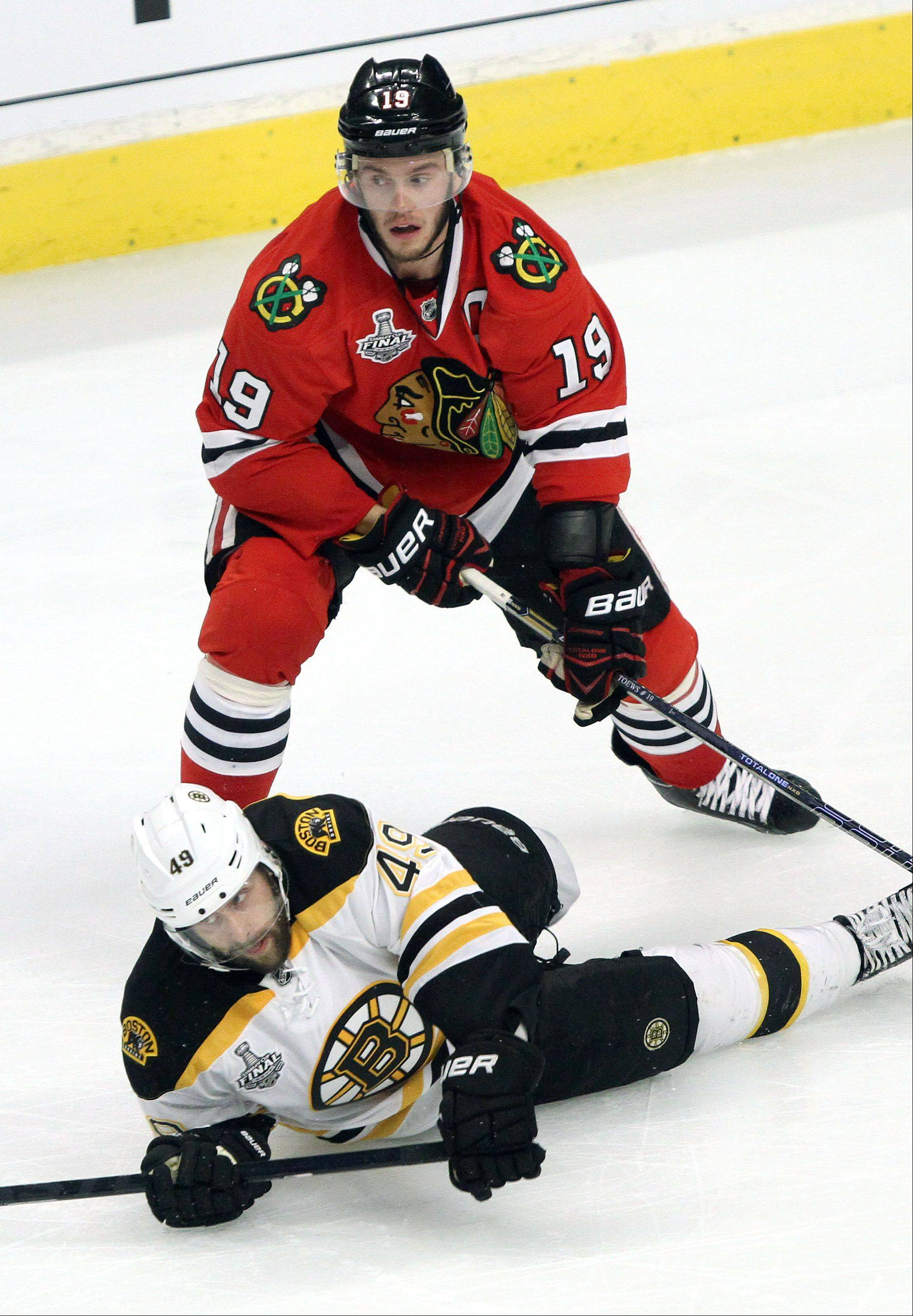 Chicago Blackhawks center Jonathan Toews knocks down Boston Bruins center Rich Peverley during game 2 of the Stanley Cup Finals against the Boston Bruins at the United Center in Chicago Saturday.