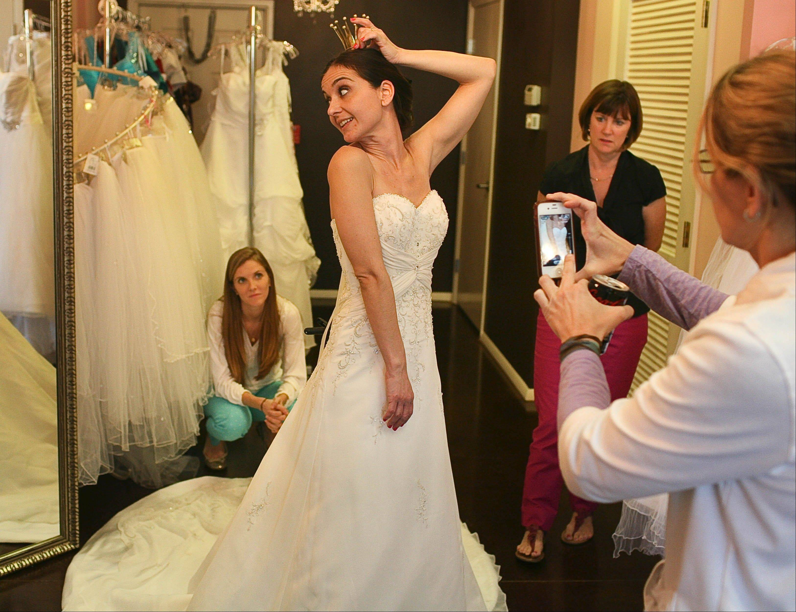 Nikki Rodriguez tries a family heirloom crown on for size as she looks for the perfect wedding dress at Brides Against Breast Cancer in Sarasota, Fla.