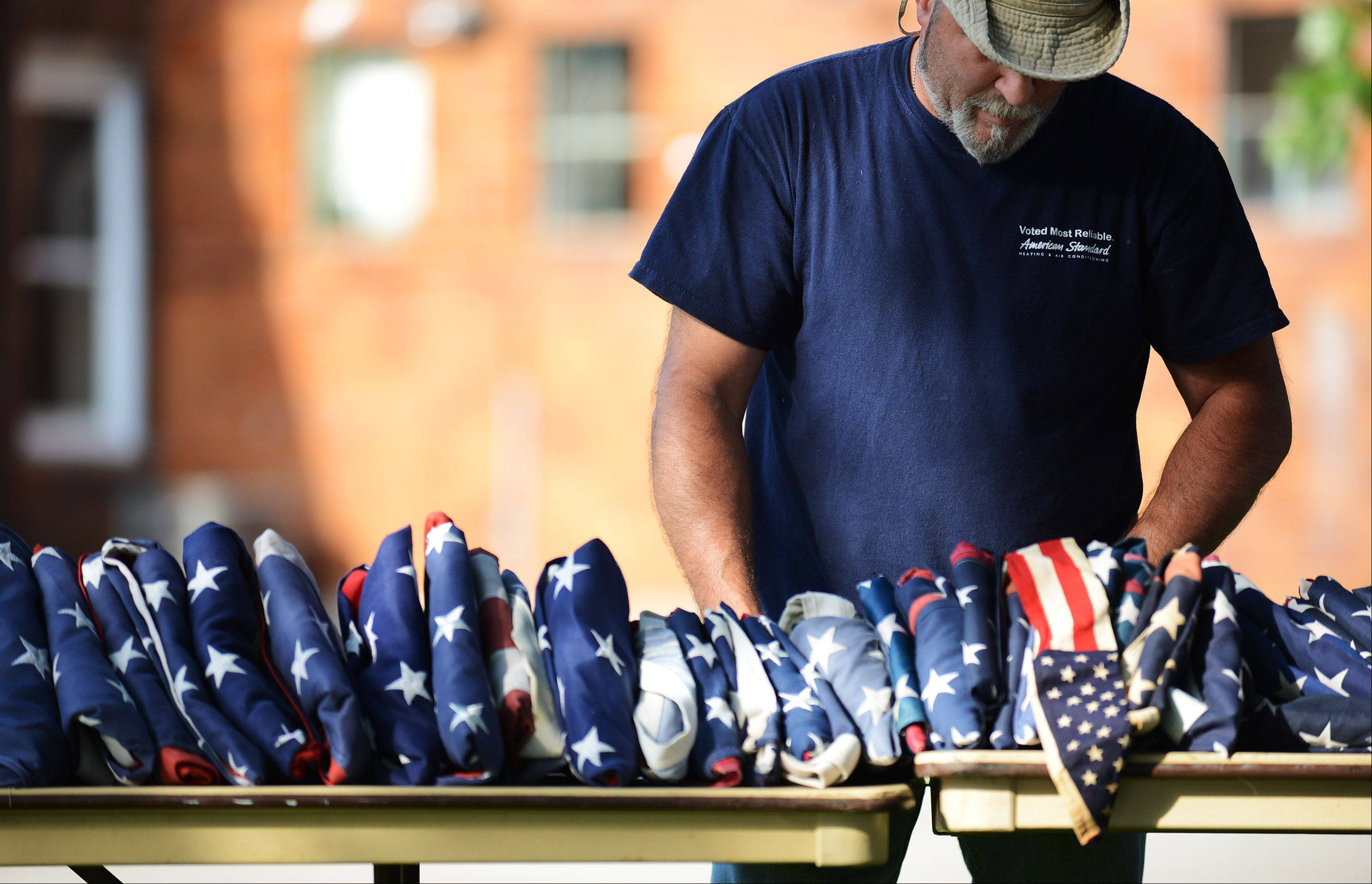 Mike Carter, of Sugar Grove, carefully arranges flags at a flag disposal ceremony Friday. The event was held at the Sugar Grove Veterans Park, where people could respectfully dispose of their warn-out United States flags.