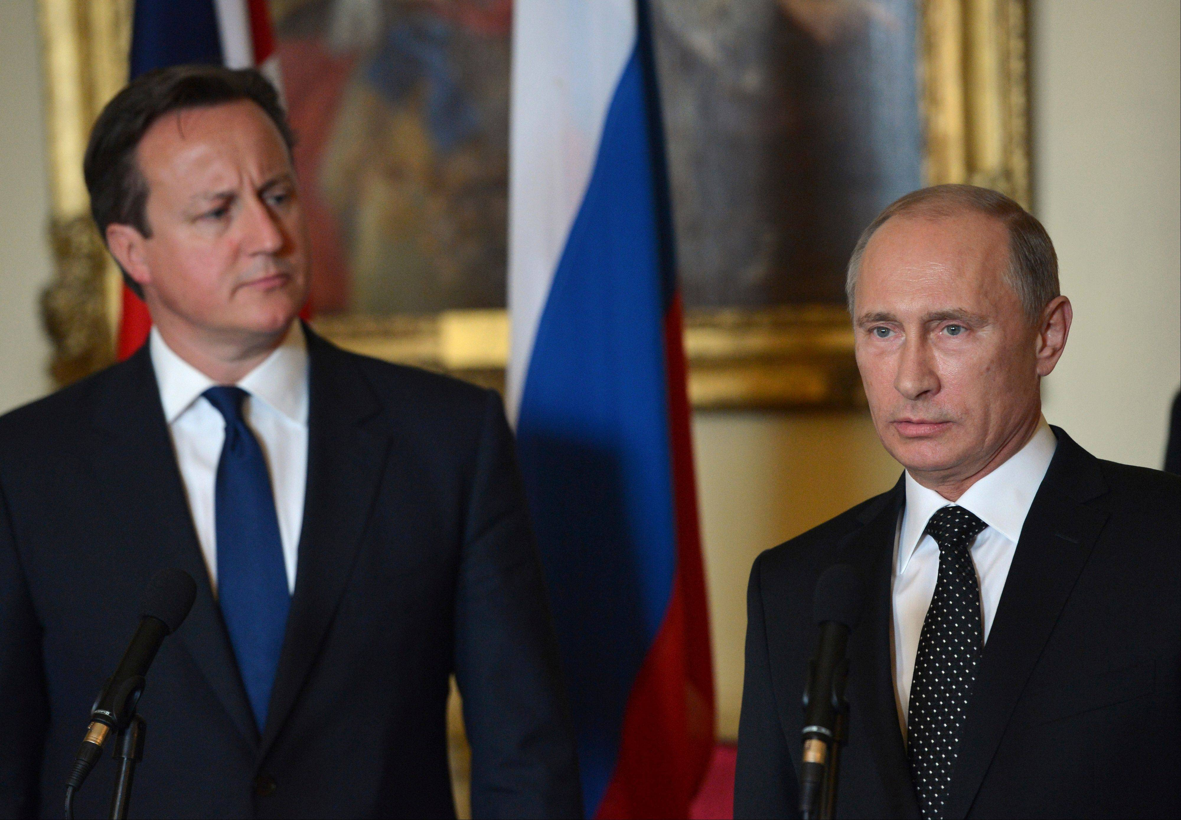British Prime Minister David Cameron, left, stands with Russian President Vladimir Putin during a press conference at 10 Downing Street in London, Sunday. Cameron had talks with Russian President Putin on the Syrian crisis amid fears that differences between Moscow and the West are pushing the two sides toward a new Cold War.