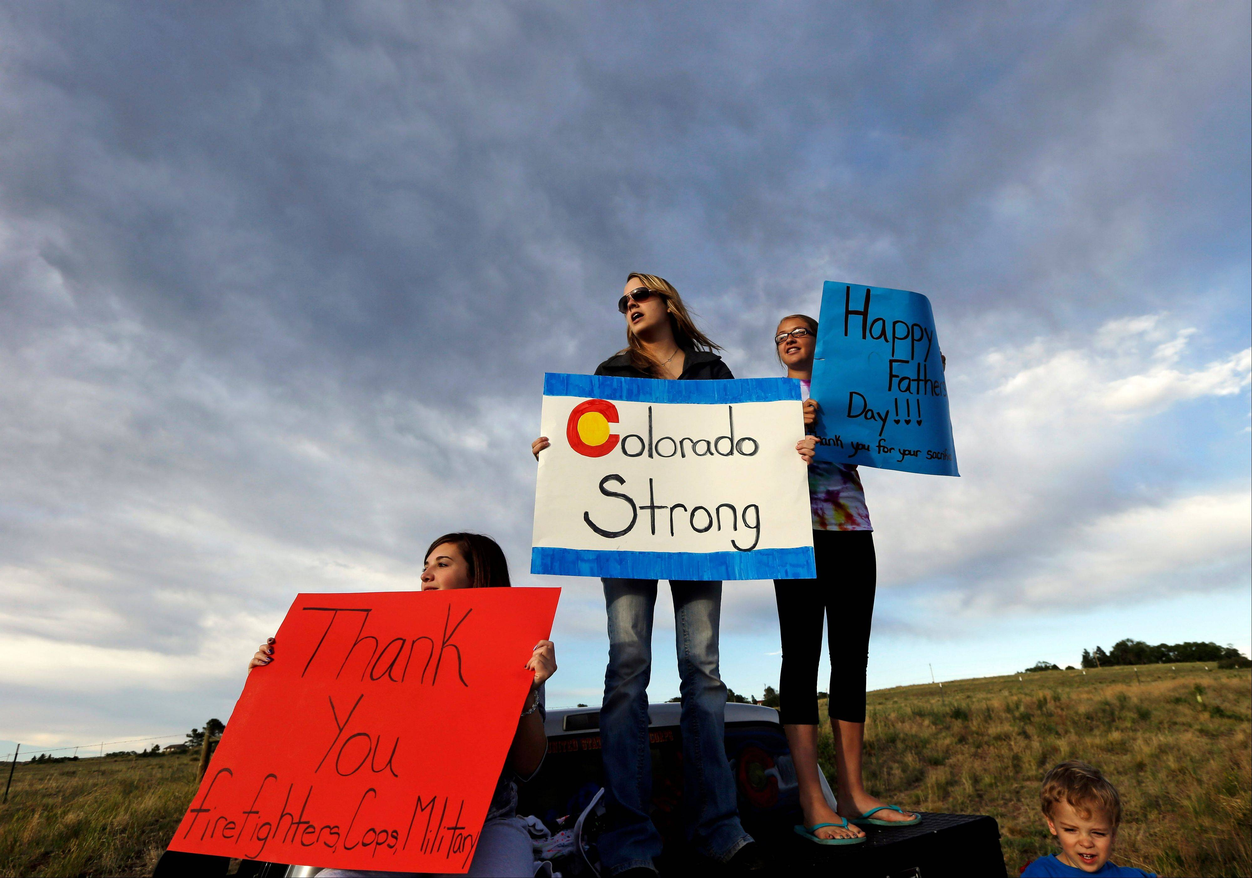 Black Forest resident Kristin Brown, left, who�s family lost their home in the wildfire, is joined by Ashley Clipp, Kaitlyn Barlow and Ashley�s son Jackson, 2, as they support first responders outside of a fire camp in Colorado Springs, Colo., Sunday.