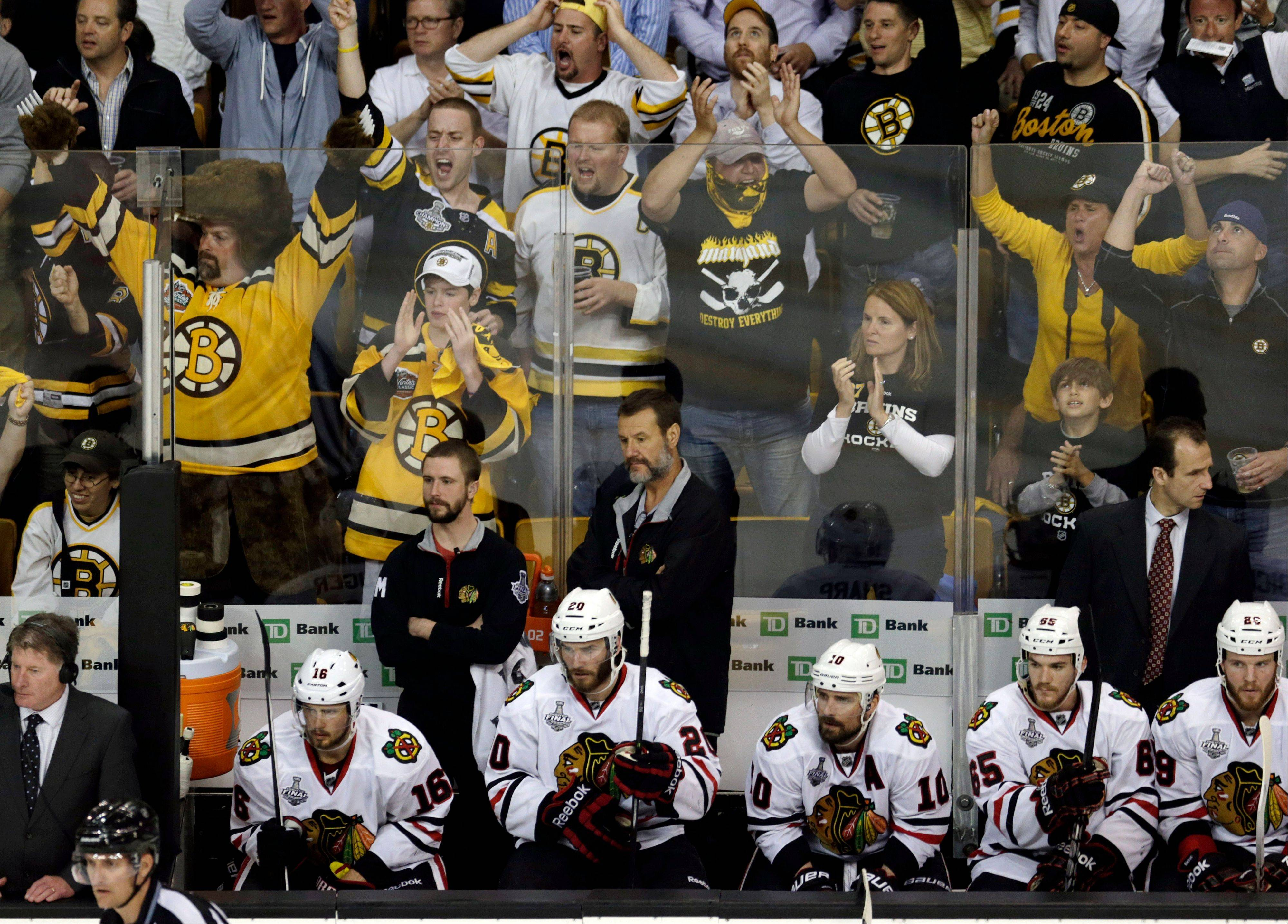 Bruins fans cheer behind the Blackhawks� bench during the third period of Game 3 Monday in Boston.