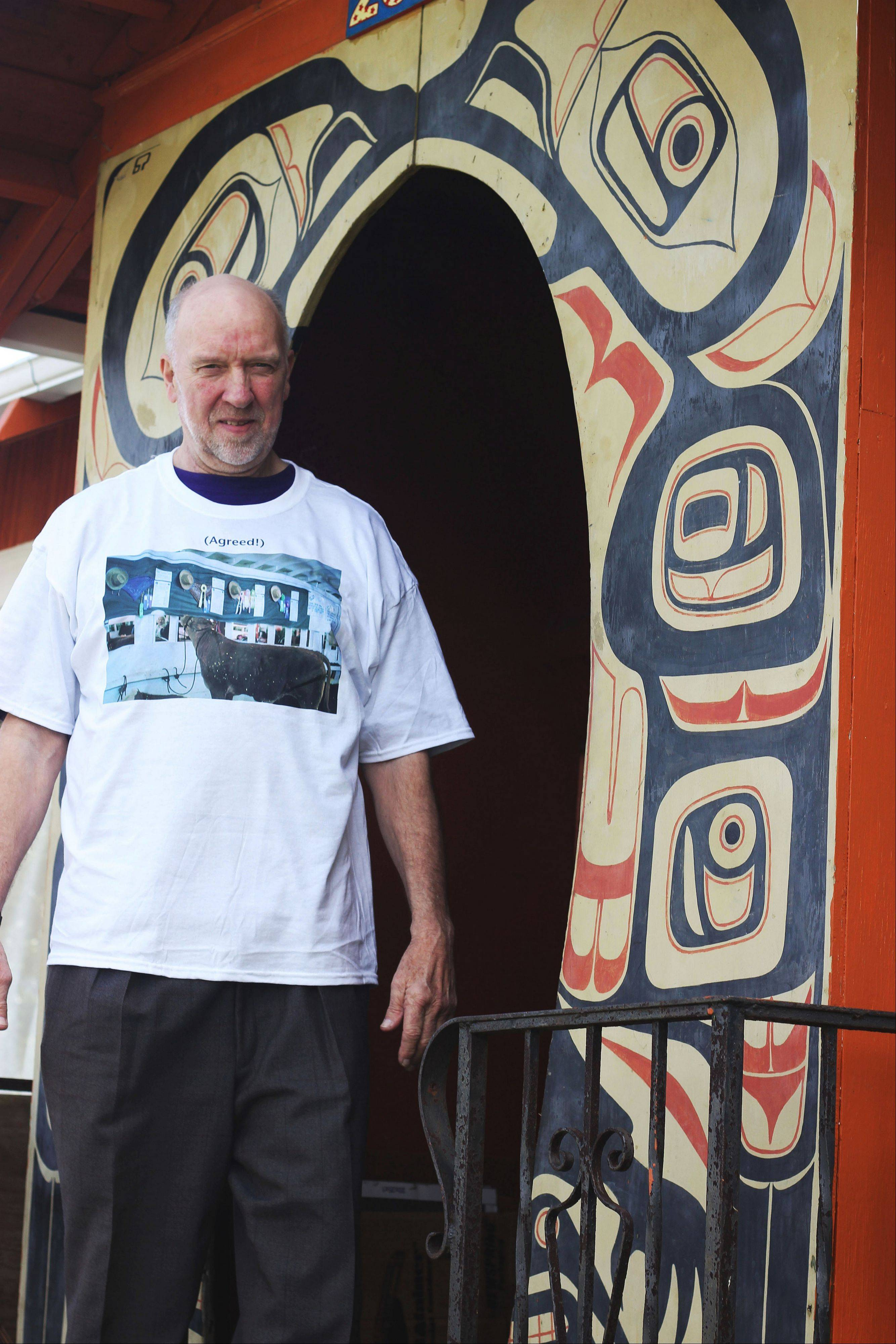 "Ormbrek stands beneath the doorway of his house, which was known as ""The Totem House"" among local residents for its enormous Tlingit Haida painting on the side. The totem archway is the last remaining vestige of the totem artwork."