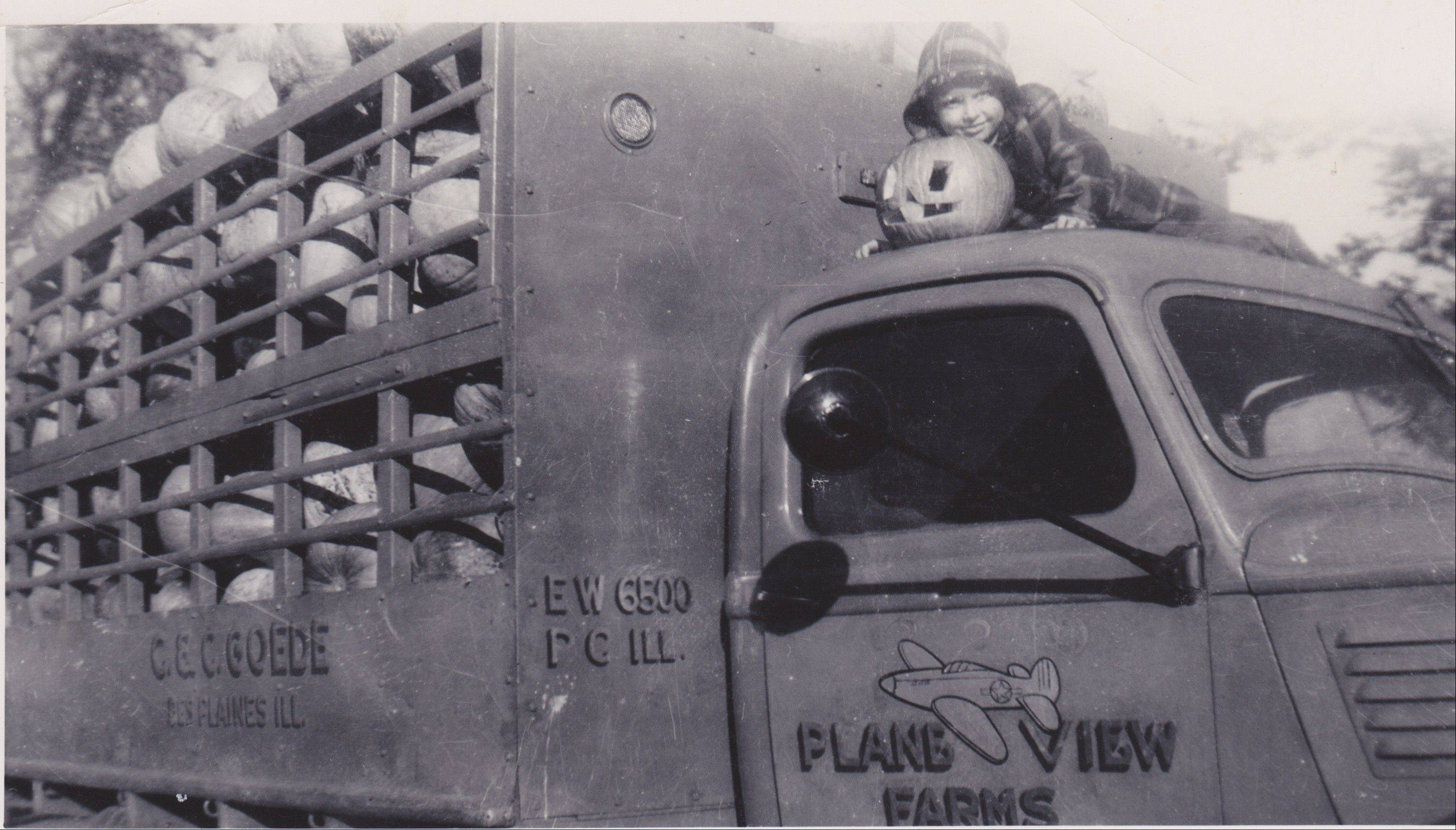 Wayne Goede, in 1942, with a carved pumpkin atop the farm truck.