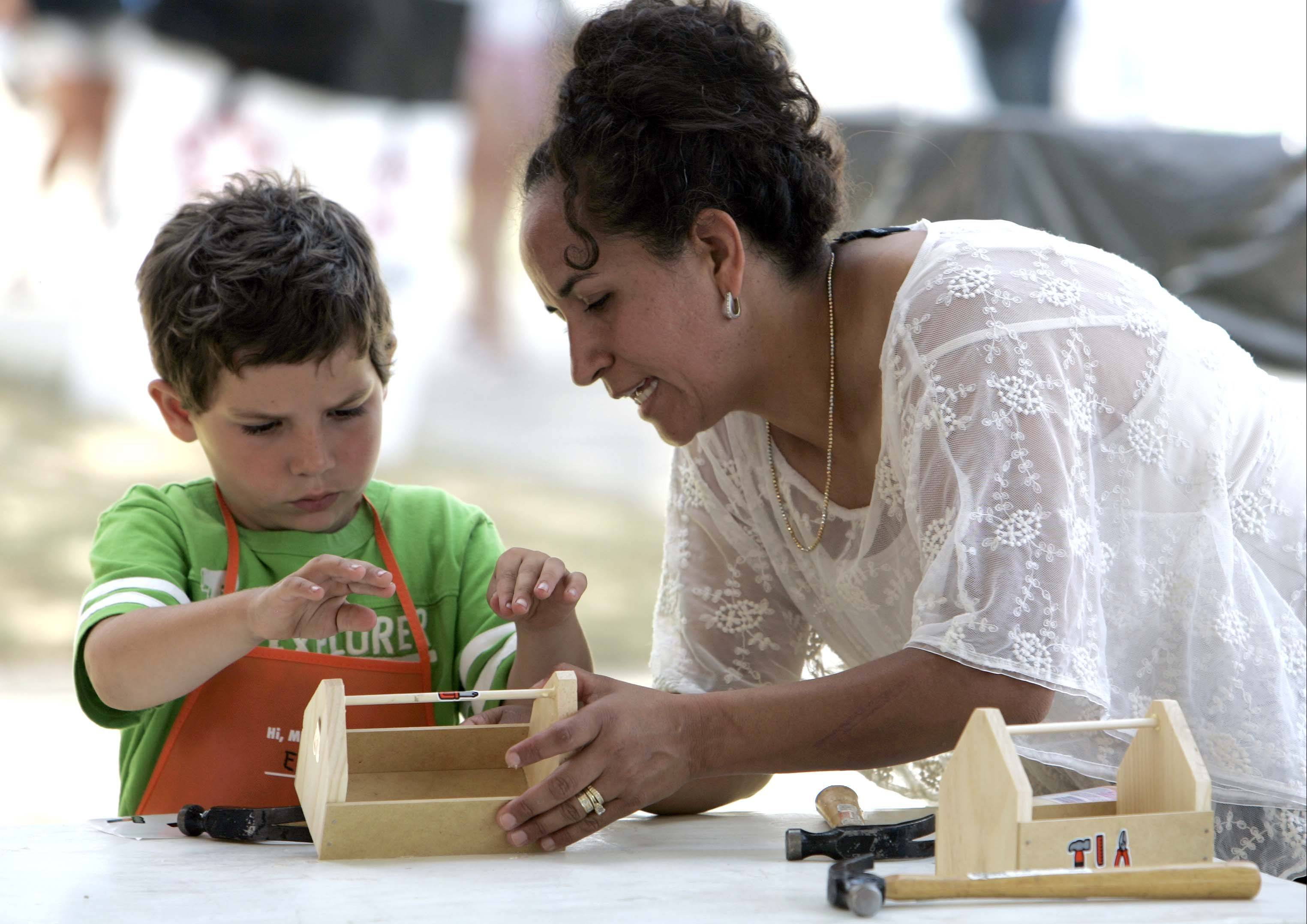 Five-year-old Eric Stoffels of Batavia gets some help from his mom Diocelina to put the finishing touches on his tool box at the Creation Station during last year's Swedish Days festival.