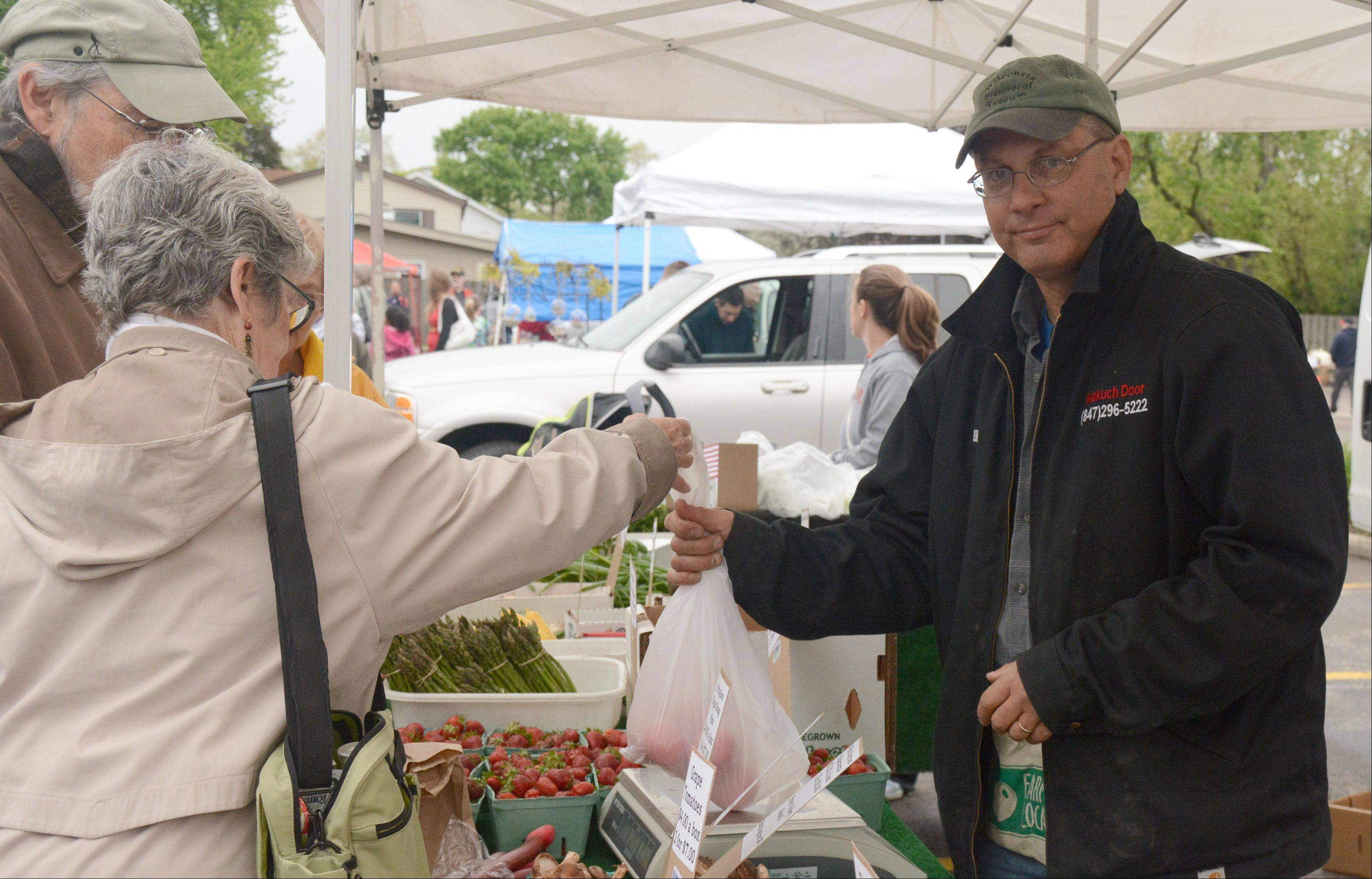 Bill Makuch sells fruit and vegetables at the Rolling Meadows' Farmers Market/Food Truck inauguration.
