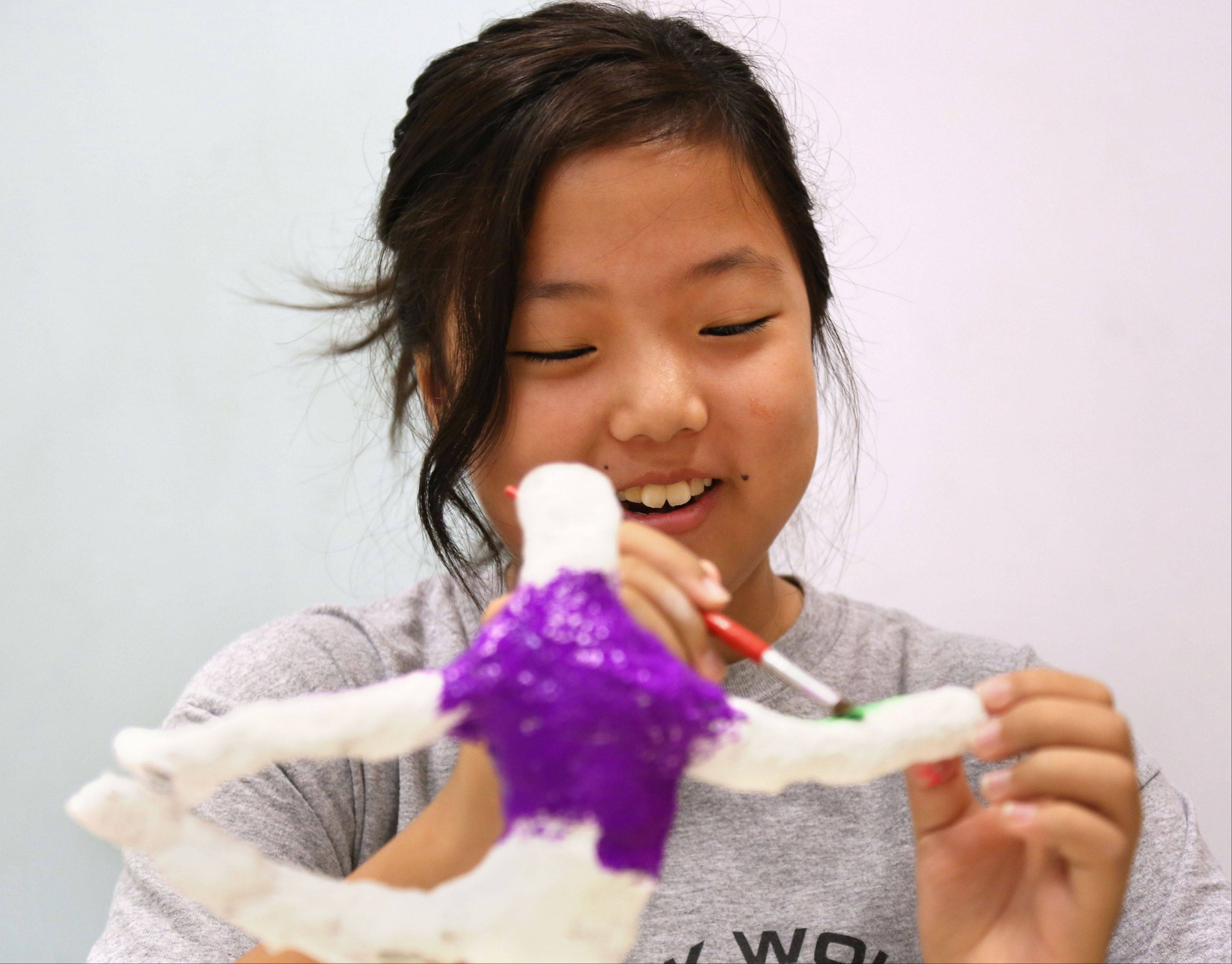 Eleven-year-old Youjin Kim paints a sculpture she made at Summer Academy, one of the enrichment classes offered at Frederick School.