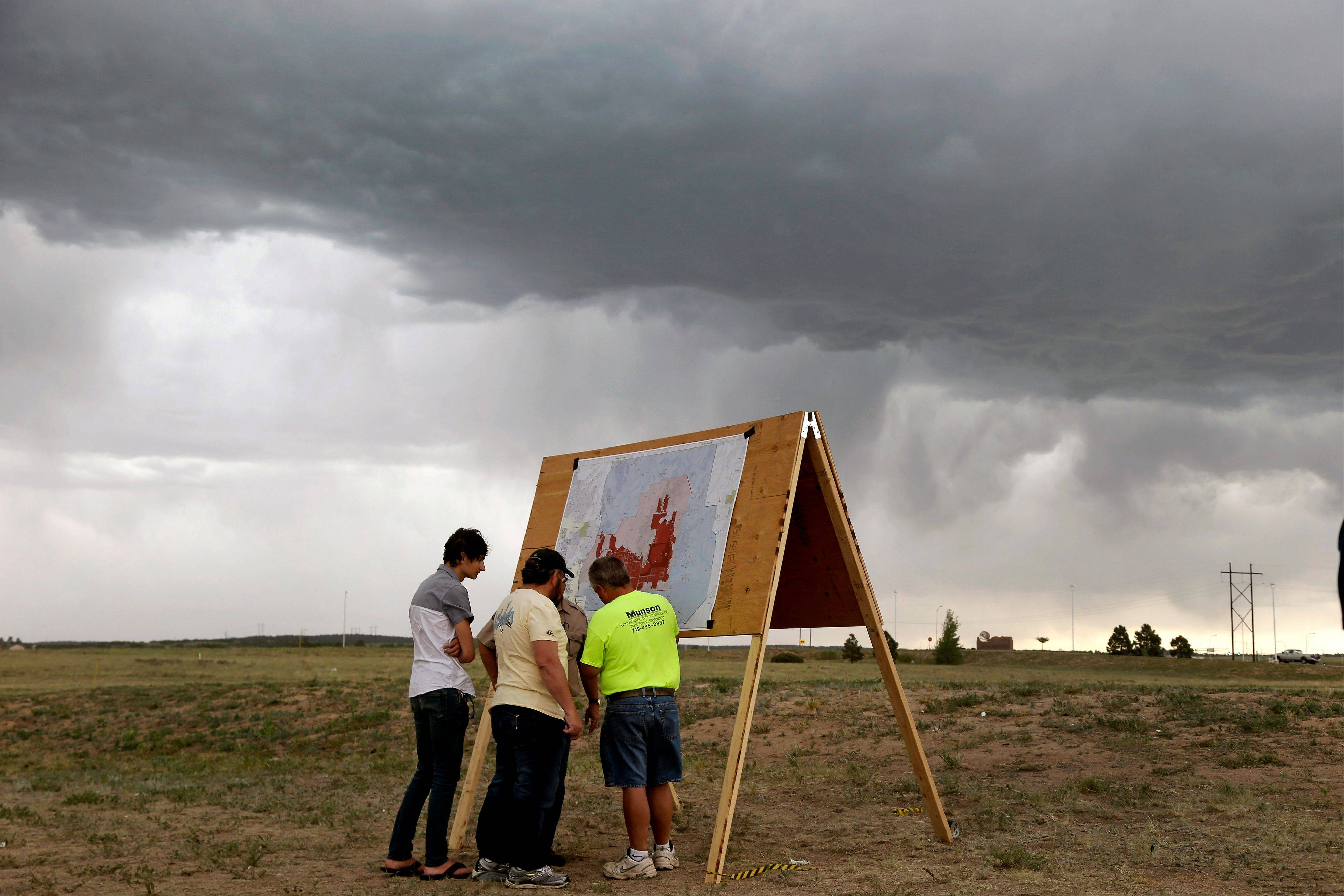 Residents look at a map detailing the progress of the Black Forest wildfire Sunday in Colorado Springs, Colo. Fire crews were putting out hot spots Sunday to prevent flare ups in heavily wooded Black Forest, where hundreds of houses have been destroyed.