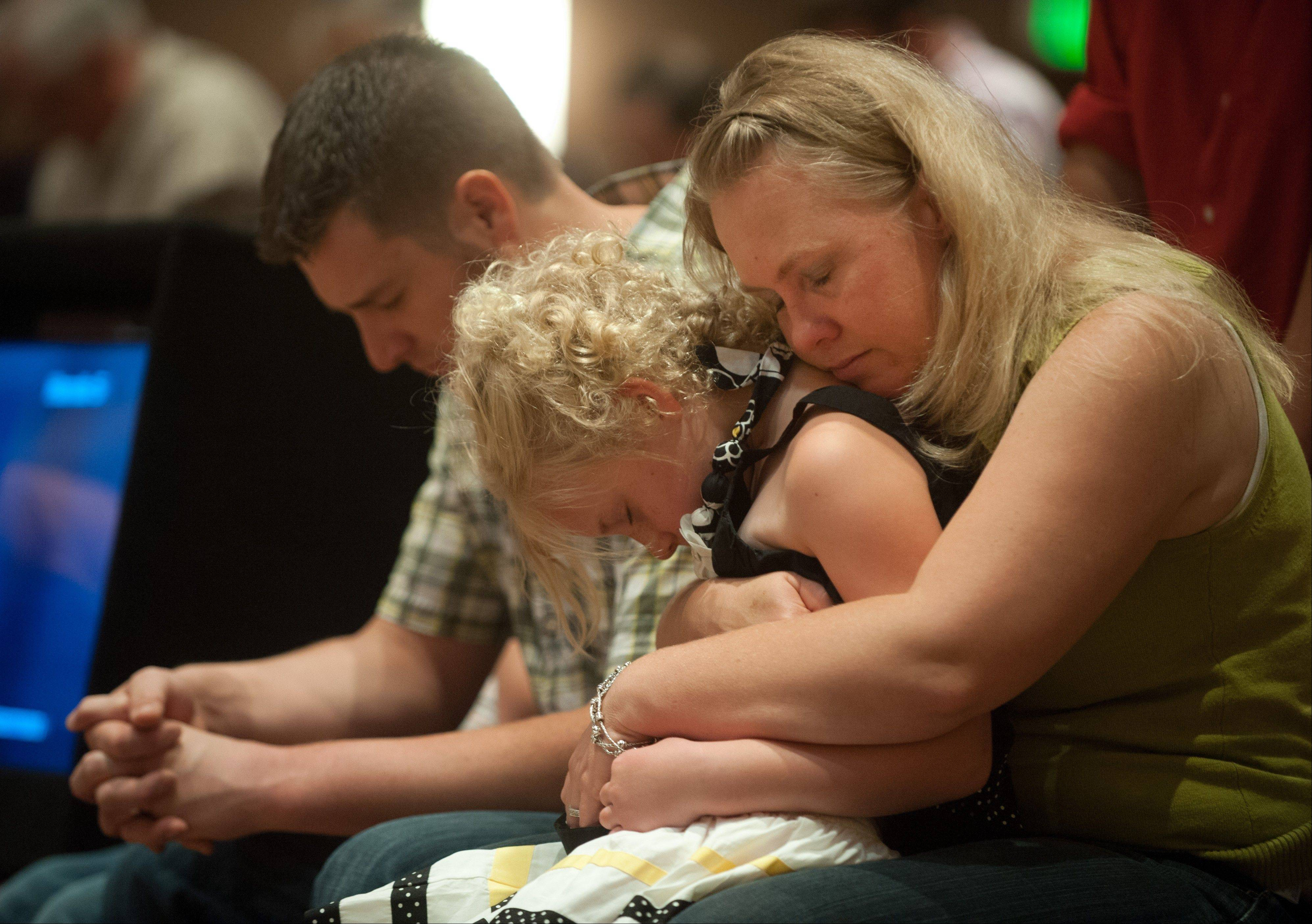 Lara Stern, right, prays with her daughter, Alana, 8, and husband, Samuel Stern, Sunday during a community prayer and praise worship service at First Baptist Church on Black Forest Road northeast of Colorado Springs, Colo. The Stern family and at least 10 other families at the church lost their homes to the Black Forest fire.