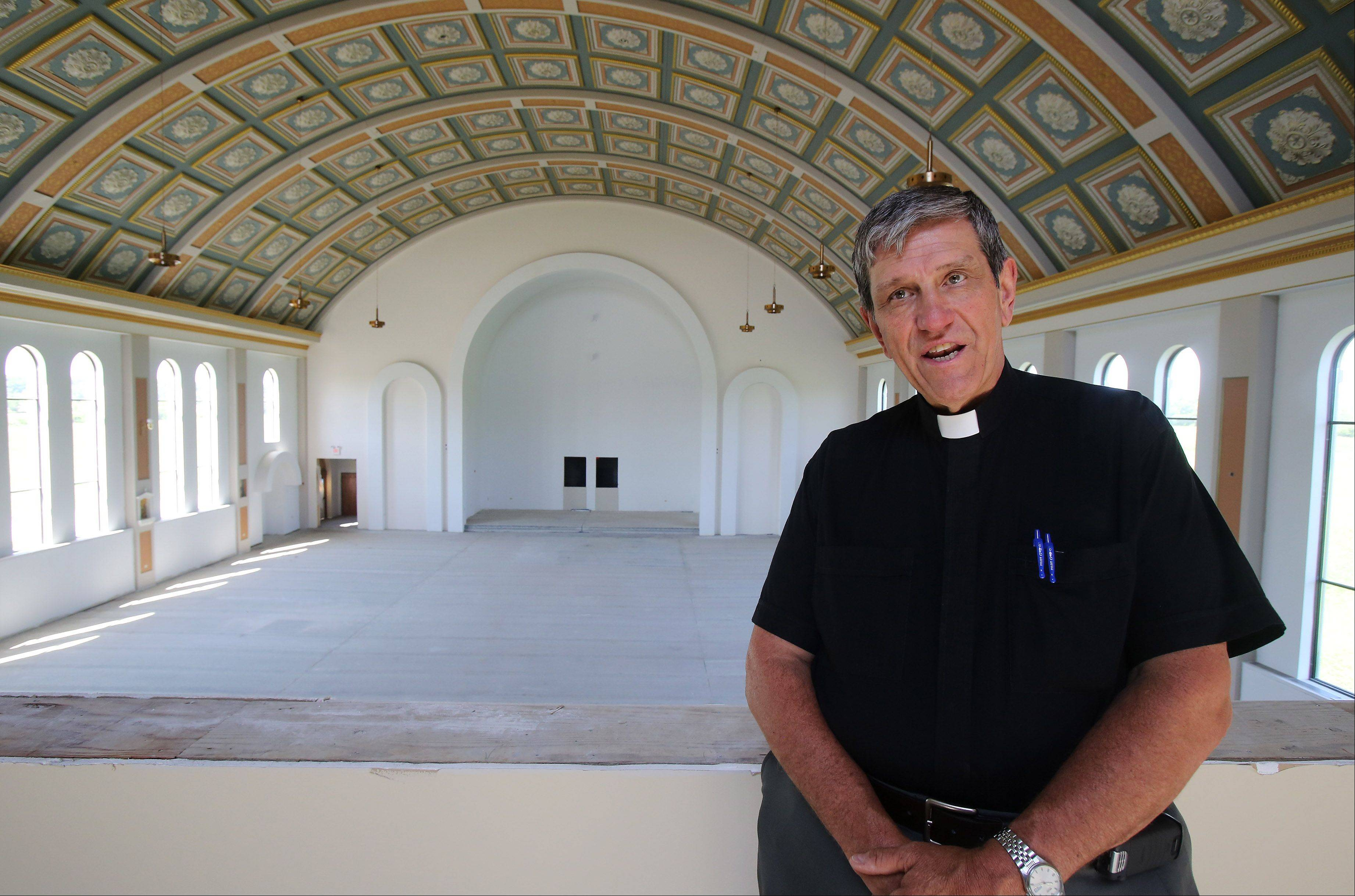 The Rev. John Jamnicky, pastor of St. Raphael the Archangel Catholic Church, discusses plans for the new church building in Old Mill Creek. Services have been held in a converted machine shop on a farm on Route 173 since the parish was established in 2007.