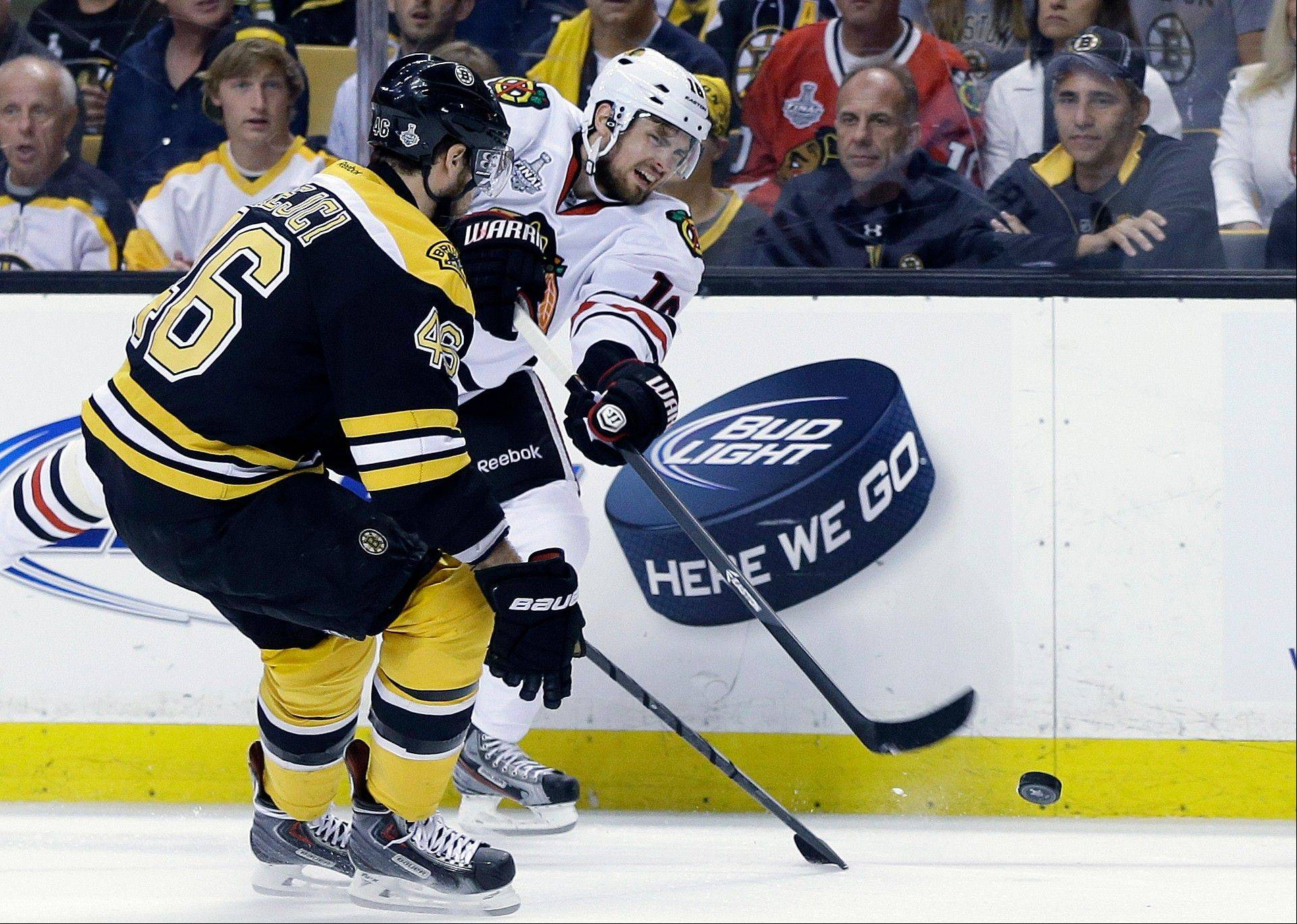 Chicago Blackhawks center Marcus Kruger, right, fires the puck past Boston Bruins center David Krejci (46), of the Czech Republic, during the first period in Game 3 of the NHL hockey Stanley Cup Finals.