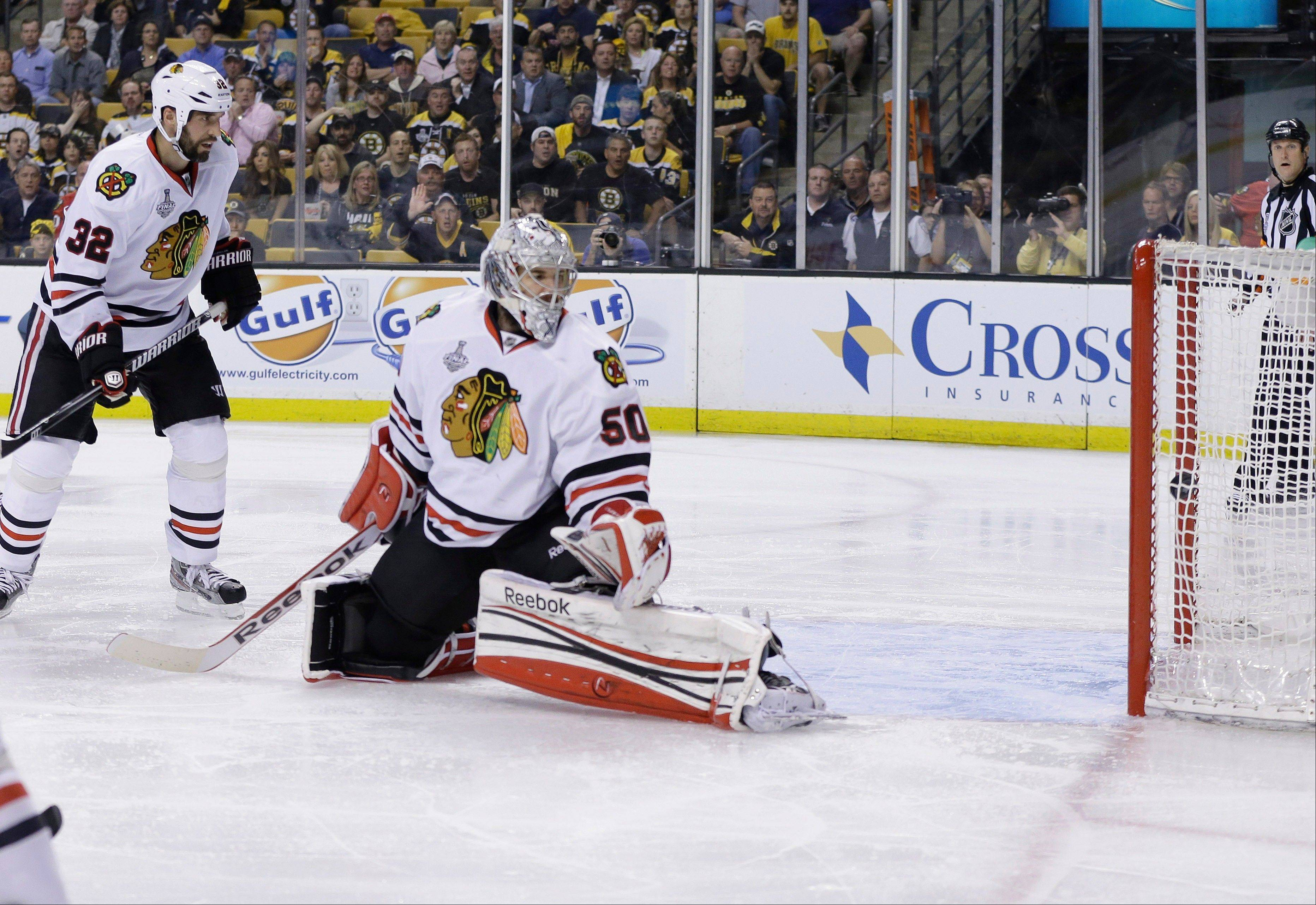 The puck from Boston Bruins' Daniel Paille, not seen, settles into the net past Chicago Blackhawks goalie Corey Crawford (50) and defenseman Michal Rozsival (32), of the Czech Republic, during the second period in Game 3 of the NHL hockey Stanley Cup Finals.