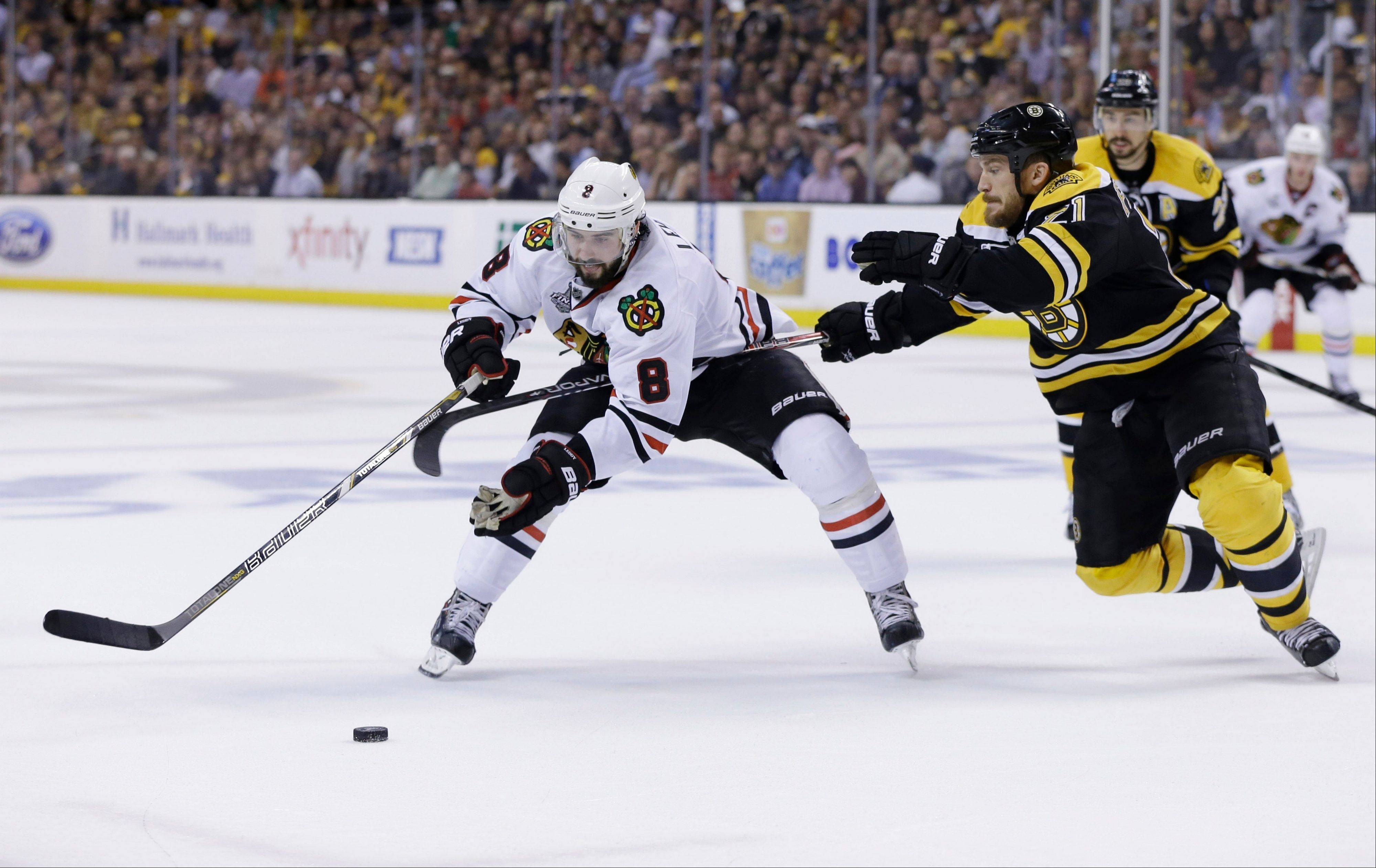Boston Bruins defenseman Andrew Ference (21) defends against Chicago Blackhawks defenseman Nick Leddy (8) during the third period in Game 3 of the NHL hockey Stanley Cup Finals.