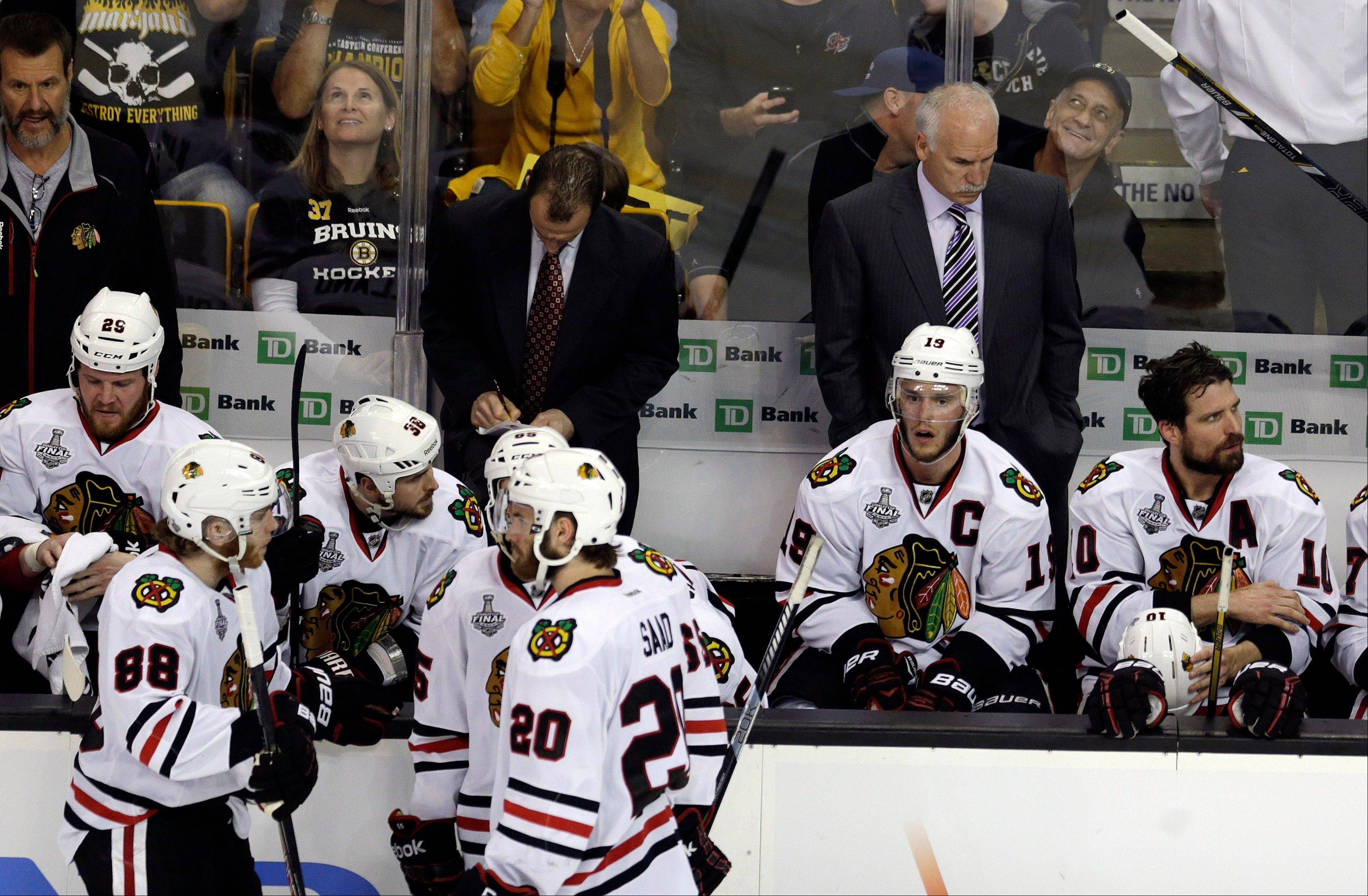 Chicago Blackhawks head coach Joel Quenneville, right, team captain Jonathan Toews (19) and their team pause during a break in pay in the third period in Game 3 of the NHL hockey Stanley Cup Finals against the Boston Bruins.