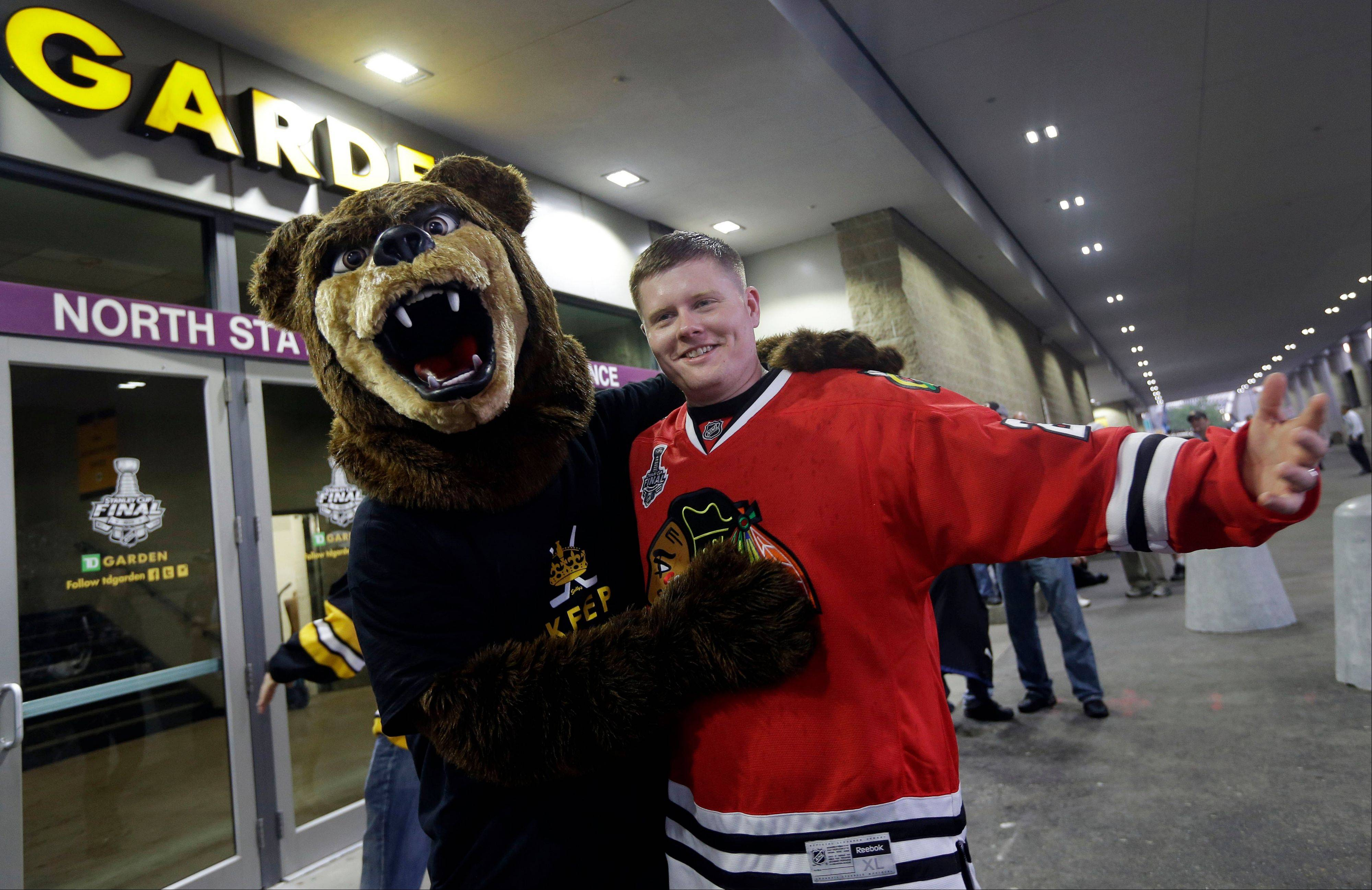 Boston Bruins fan Matt Kona, left, of Boston, wearing a bear costume poses with Chicago Blackhawks fan T.J. Budka, right, of Ayer, Mass., outside TD Garden in Boston before Game 3 of the NHL hockey Stanley Cup Finals between the Bruins and the Blackhawks Monday, June 17, 2013.