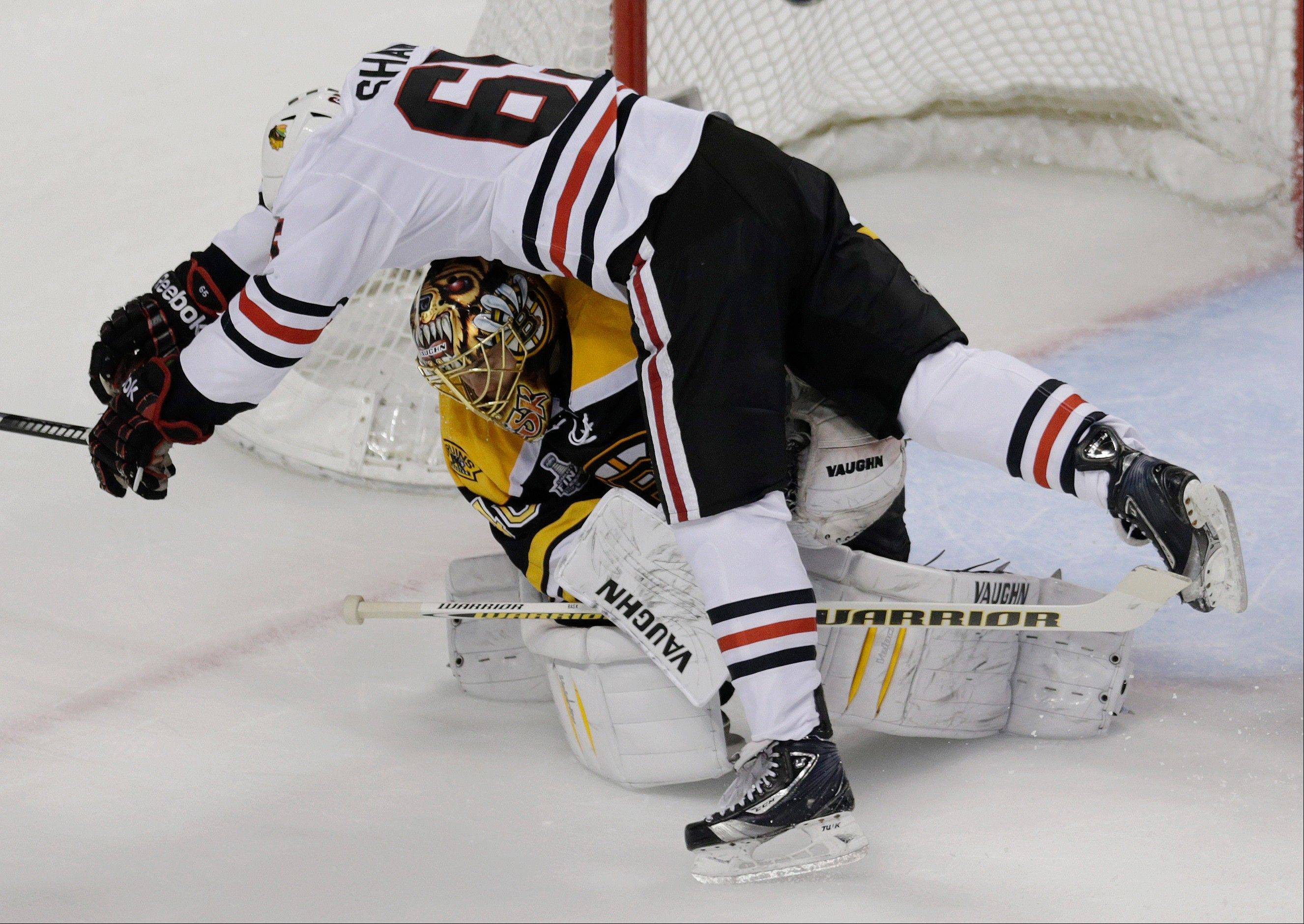Chicago Blackhawks center Andrew Shaw (65) collides with Boston Bruins goalie Tuukka Rask, underneath, of Finland, during the first period in Game 3 of the NHL hockey Stanley Cup Finals.