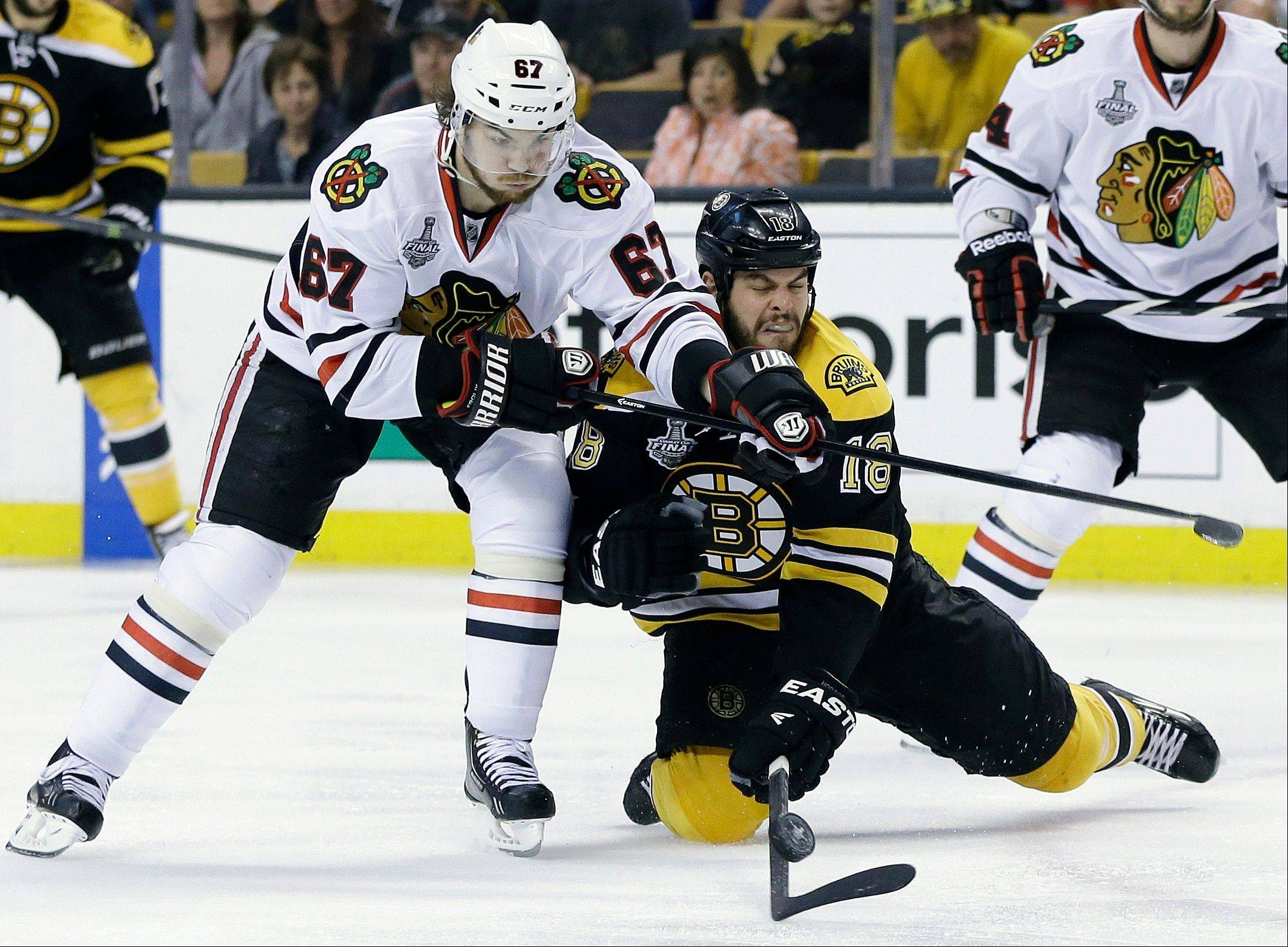 Chicago Blackhawks center Michael Frolik (67), of the Czech Republic, and Boston Bruins right wing Nathan Horton (18) scrap for the puck during the second period in Game 3 of the NHL hockey Stanley Cup Finals.