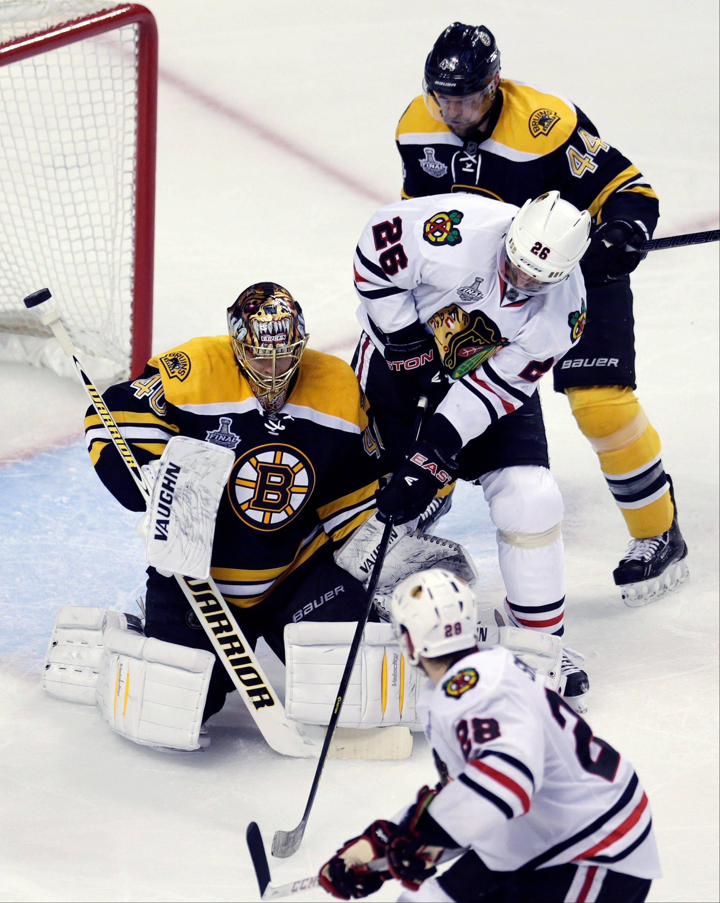 Boston Bruins goalie Tuukka Rask (40), of Finland, defends against Chicago Blackhawks center Michal Handzus (26), of Slovakia, as Bruins defenseman Dennis Seidenberg (44), of Germany, and Blackhawks right wing Ben Smith (28) surround them during the third period in Game 3 of the NHL hockey Stanley Cup Finals.