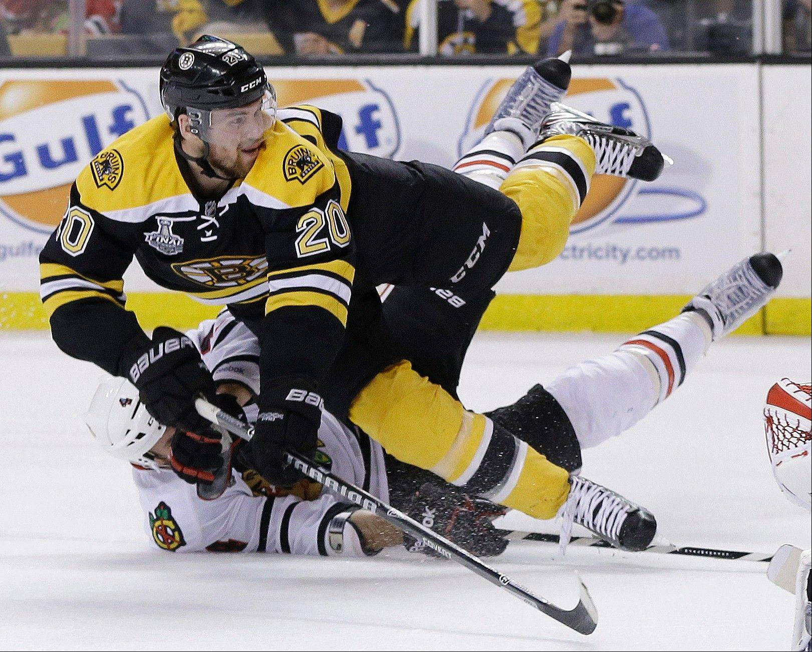 Chicago Blackhawks defenseman Niklas Hjalmarsson, bottom, of Sweden, takes down Boston Bruins left wing Daniel Paille (20) during the second period in Game 3 of the NHL hockey Stanley Cup Finals. The Bruins scored the game's second goal on the power play that followed.
