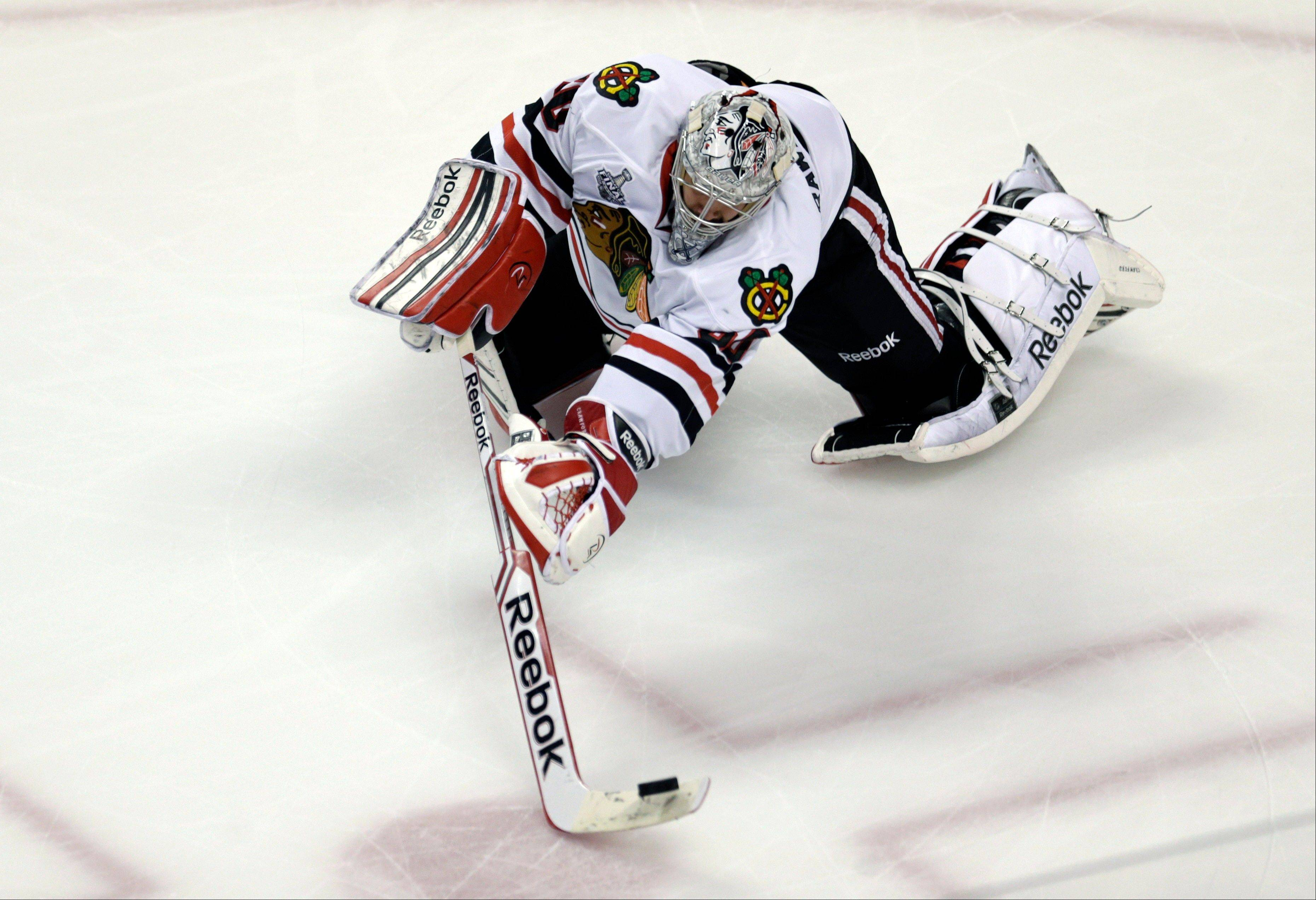 Chicago Blackhawks goalie Corey Crawford clears the puck against the Boston Bruins during the first period in Game 3 of the NHL hockey Stanley Cup Finals.