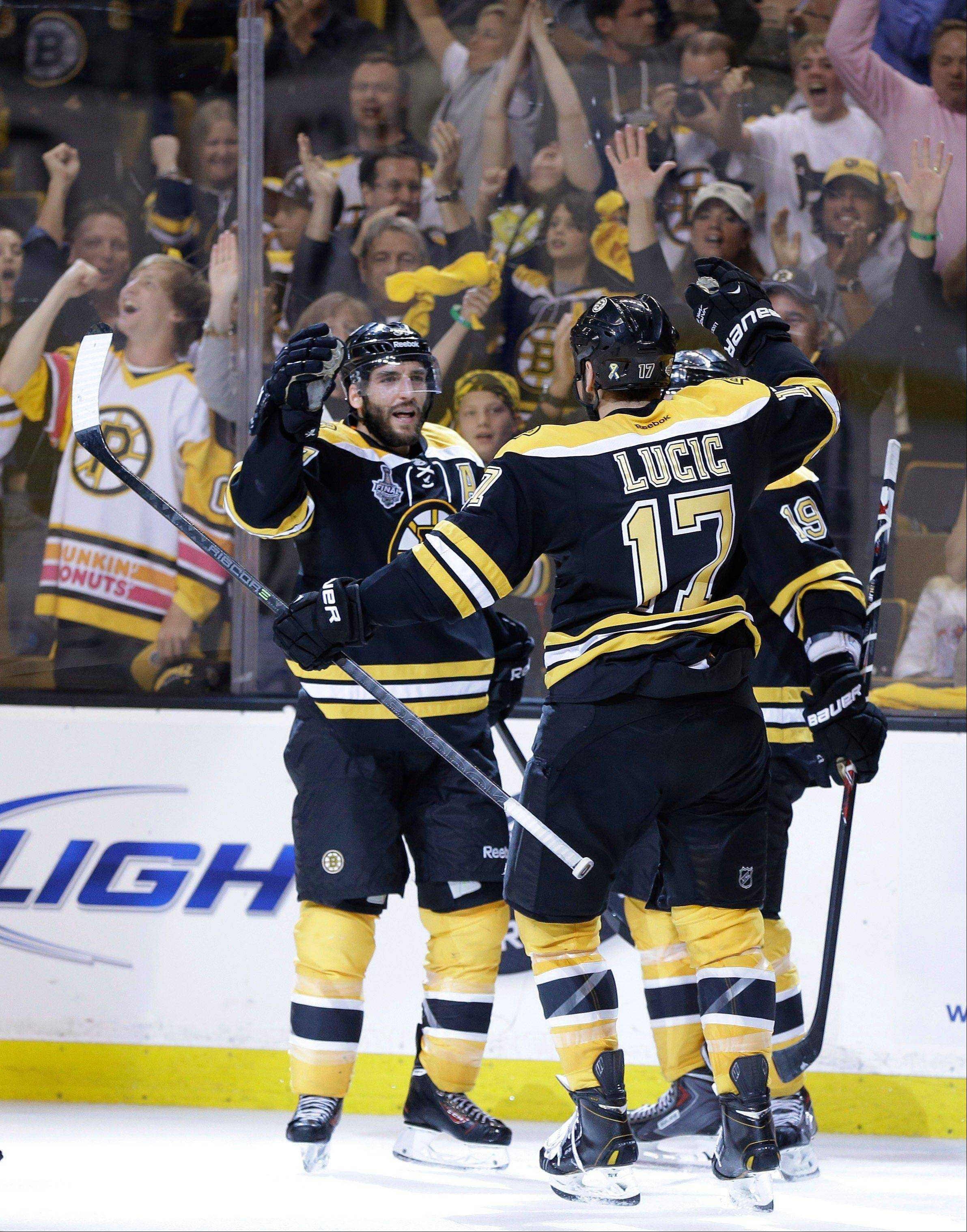 Boston Bruins center Patrice Bergeron, left, celebrates his goal against the Chicago Blackhawks with Milan Lucic (17) and Tyler Seguin (19) during the second period in Game 3 of the NHL hockey Stanley Cup Finals.