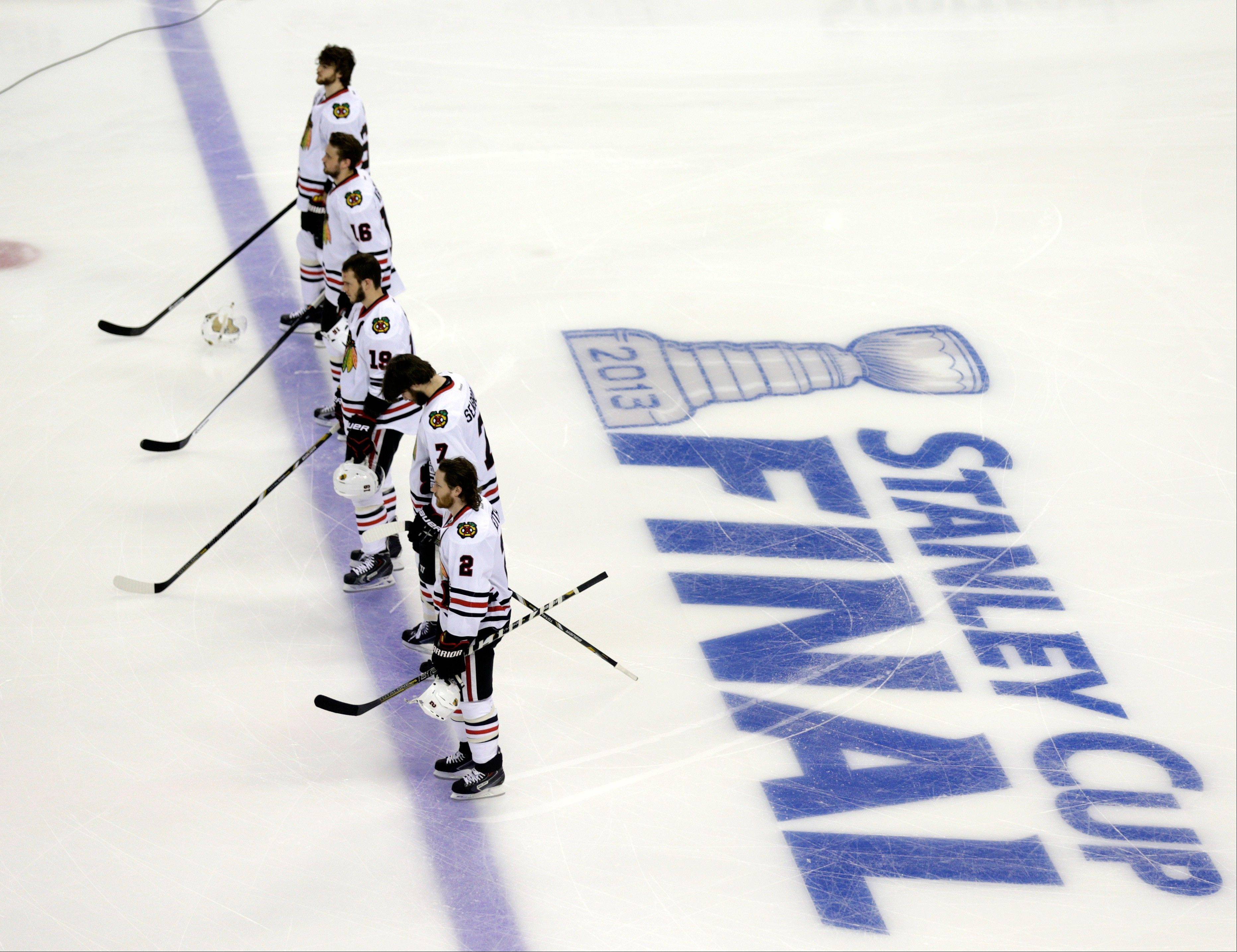 Chicago Blackhawks players stand during the national anthem before Game 3 of the NHL hockey Stanley Cup Finals against the Boston Bruins.