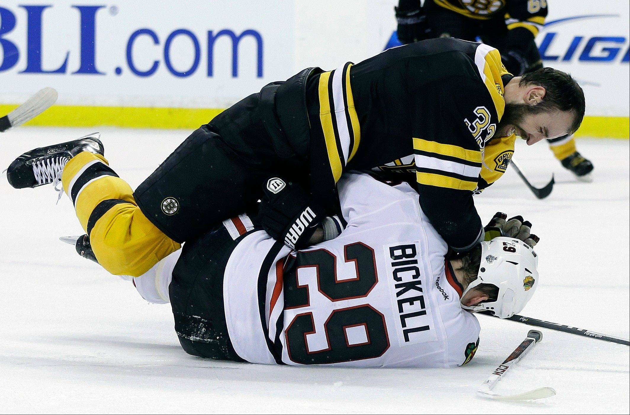 Boston Bruins defenseman Zdeno Chara (33), of Slovakia, takes down Chicago Blackhawks left wing Bryan Bickell (29) during the third period in Game 3 of the NHL hockey Stanley Cup Finals in Boston, Monday, June 17, 2013. The Bruins won 2-0.