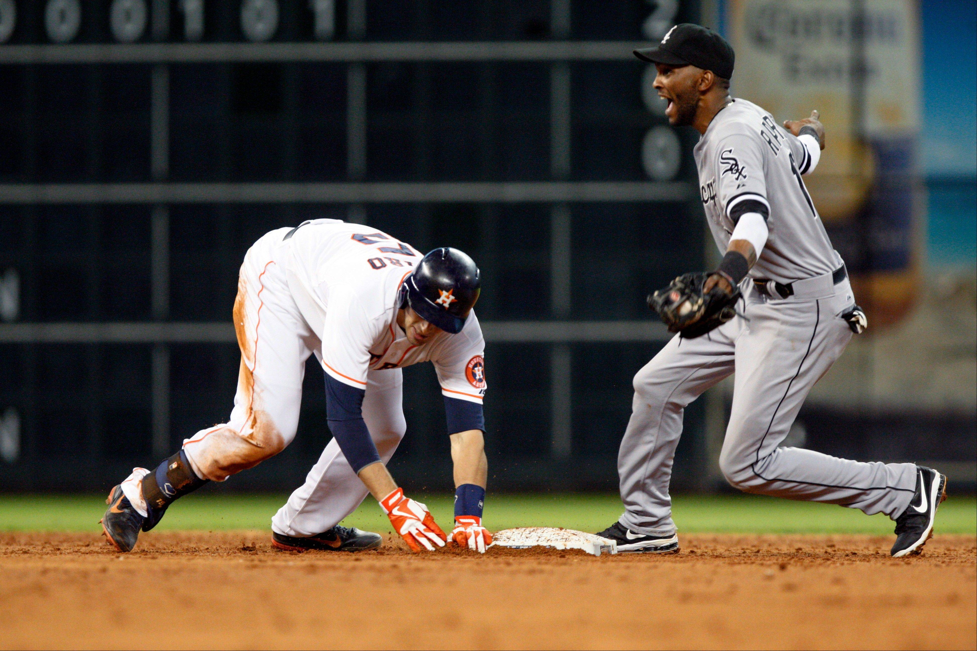 The Astros' Jason Castro eludes the tag of Alexei Ramirez in the third inning Monday in Houston.