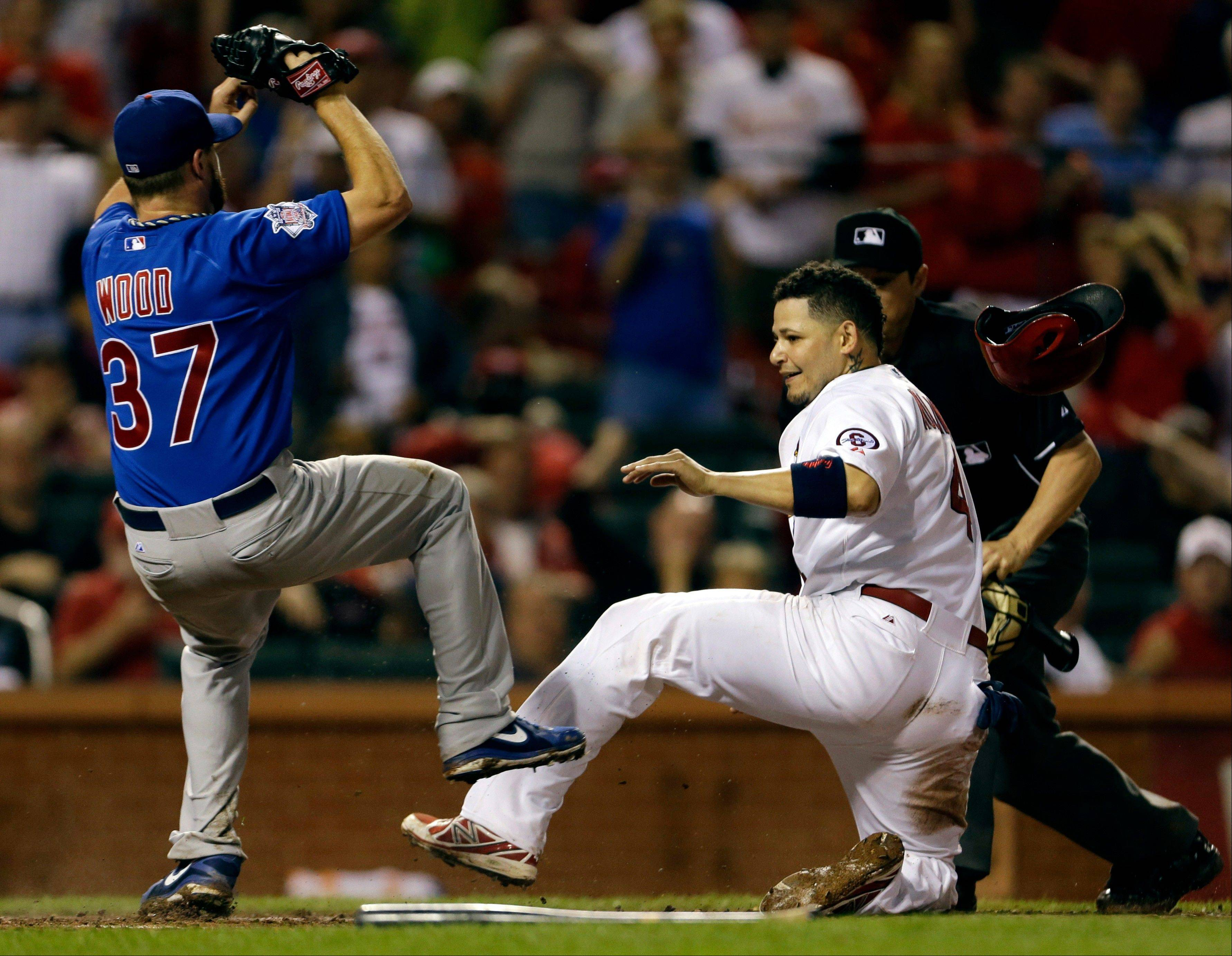 The Cardinals' Yadier Molina slides in ahead of the tag by Cubs starting pitcher Travis Wood during the seventh inning Monday in St. Louis. Molina scored on a throwing error by Cubs first baseman Anthony Rizzo.