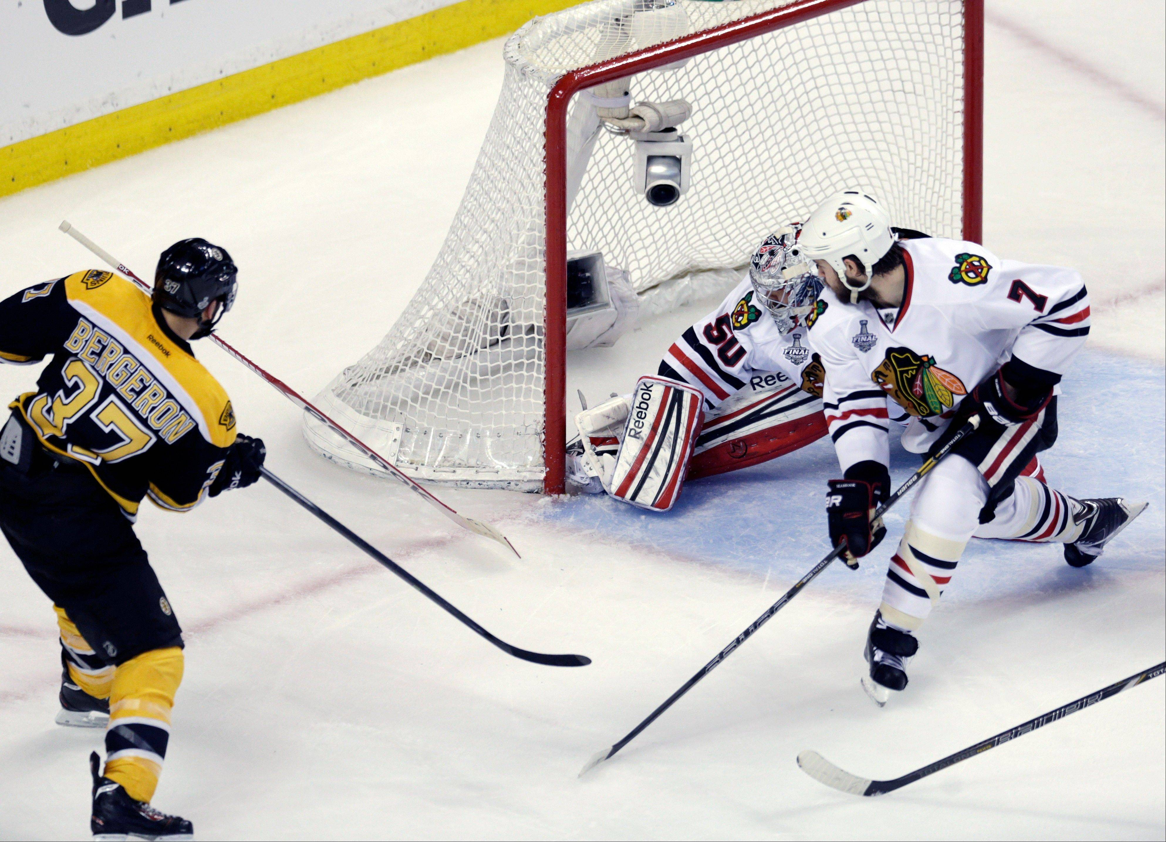 Boston Bruins center Patrice Bergeron (37) scores a goal past Chicago Blackhawks goalie Corey Crawford (50) and defenseman Brent Seabrook (7)during the second period in Game 3 of the NHL hockey Stanley Cup Finals in Boston, Monday, June 17, 2013.
