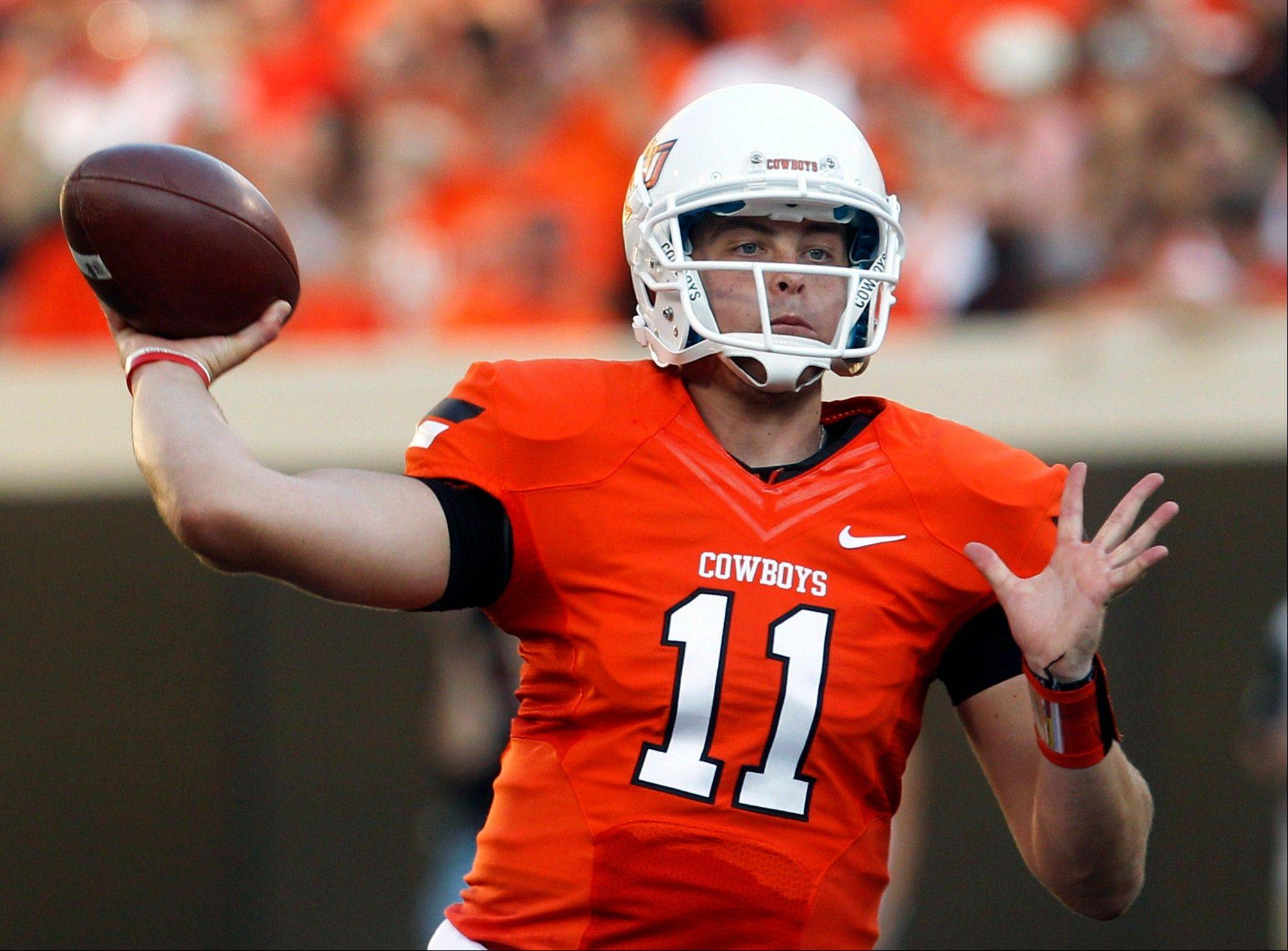 In this Sept. 1, 2012 file photo, Oklahoma State quarterback Wes Lunt throws against Savannah State during an NCAA college football game in Stillwater, Okla. Lunt will return to his home state and transfer to Illinois, a person familiar with the decision told The Associated Press on Monday, June 17, 2013.