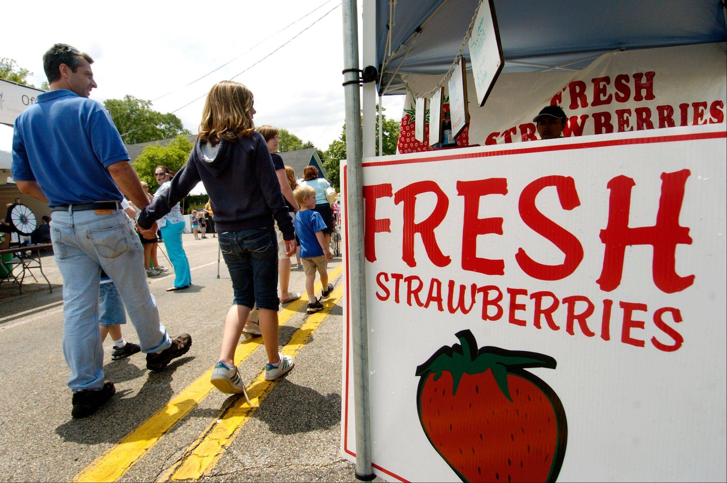 Visitors stroll past a booth with simplest treat of all -- plain strawberries.