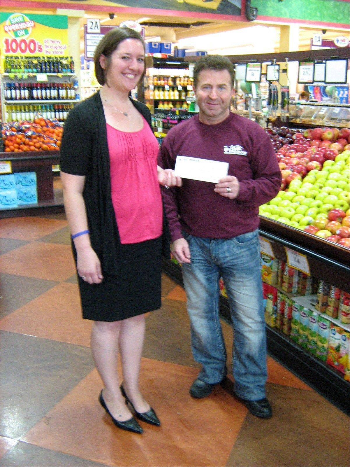Valli Produce co-founder Frank Chilelli hands a check to Julie Lorentz from the American Cancer Society. Valli Produce participated in a fundraising campaign to help support the society fight against breast cancer.