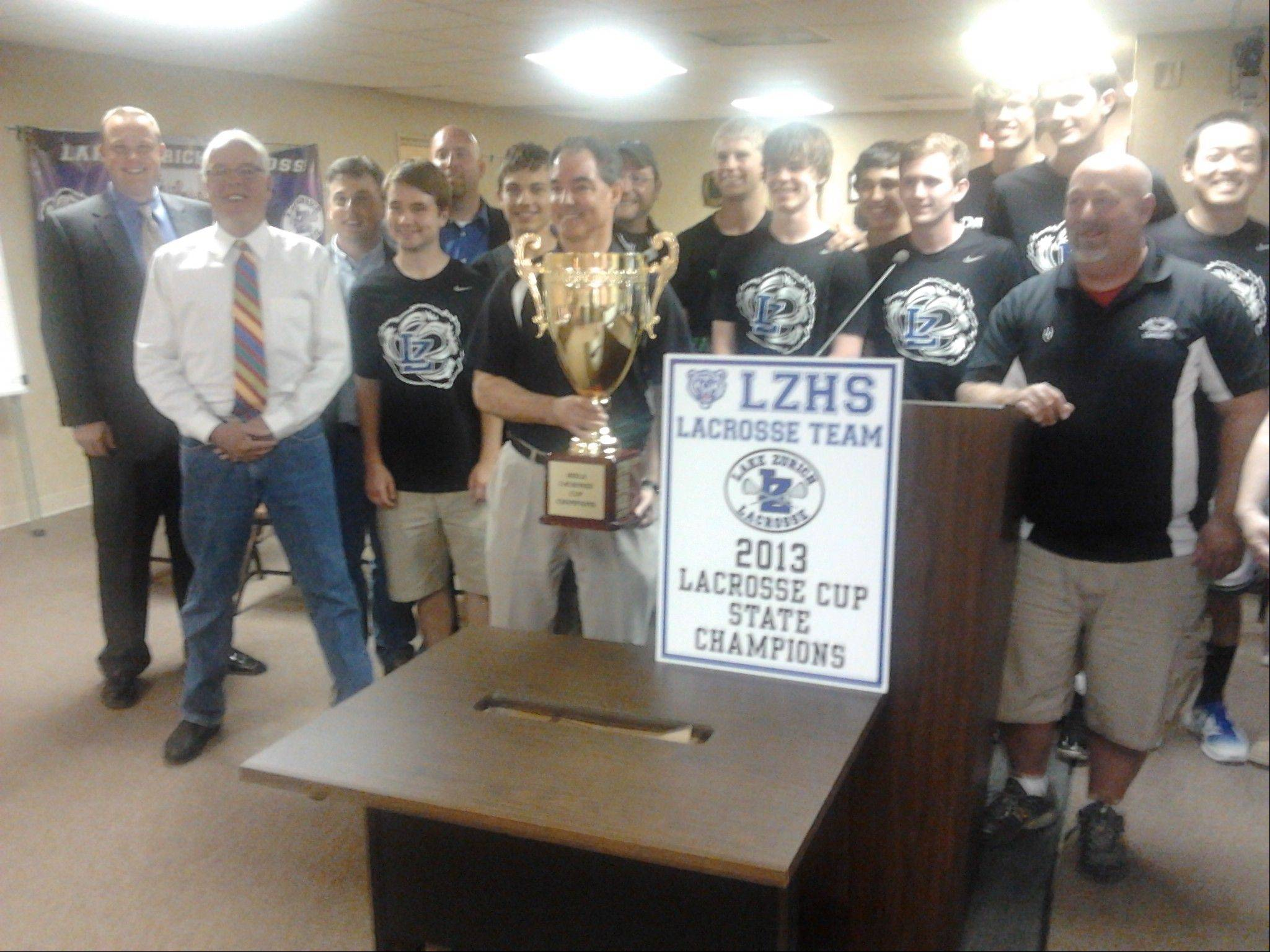 Lake Zurich Mayor Thomas Poynton (far left, in white shirt) joins Lake Zurich High School players and coaches Monday with the state championship trophy they won earlier this month. Poynton earlier read a village proclamation congratulating the team on its accomplishment.