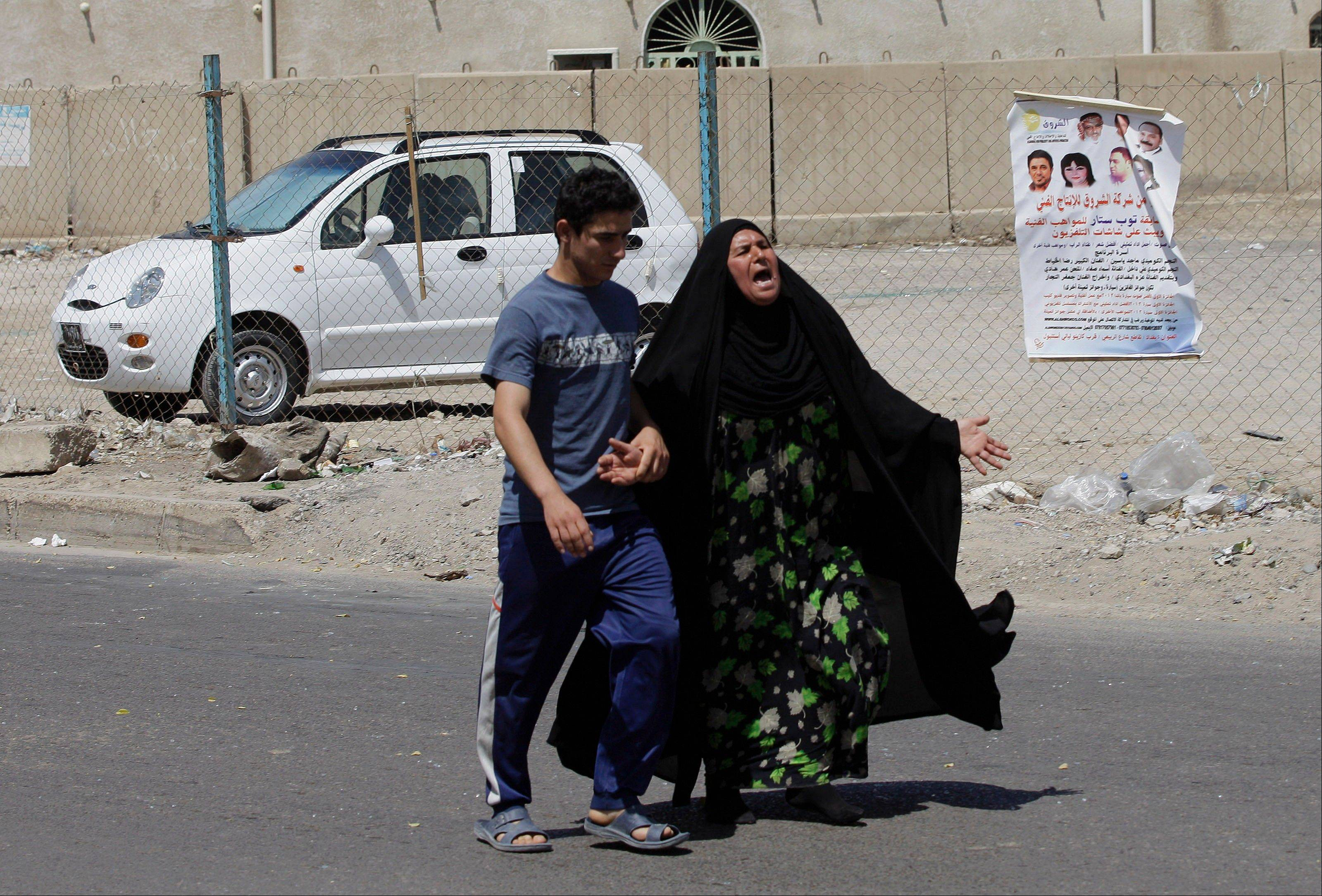 Umm Satta grieves for her slain college student son, Sattar Jabbar, near Habib al-Asadi Shiite mosque in Baghdad, Iraq, Tuesday, June 18, 2013. Two suicide bombers blew themselves up inside and near the Shiite mosque, Iraqi officials said. Most of the casualties were among students from a nearby Imam al-Sadiq University for Islamic Studies. Police officials said the university�s Shiite students usually perform their midday prayers in the targeted mosque.