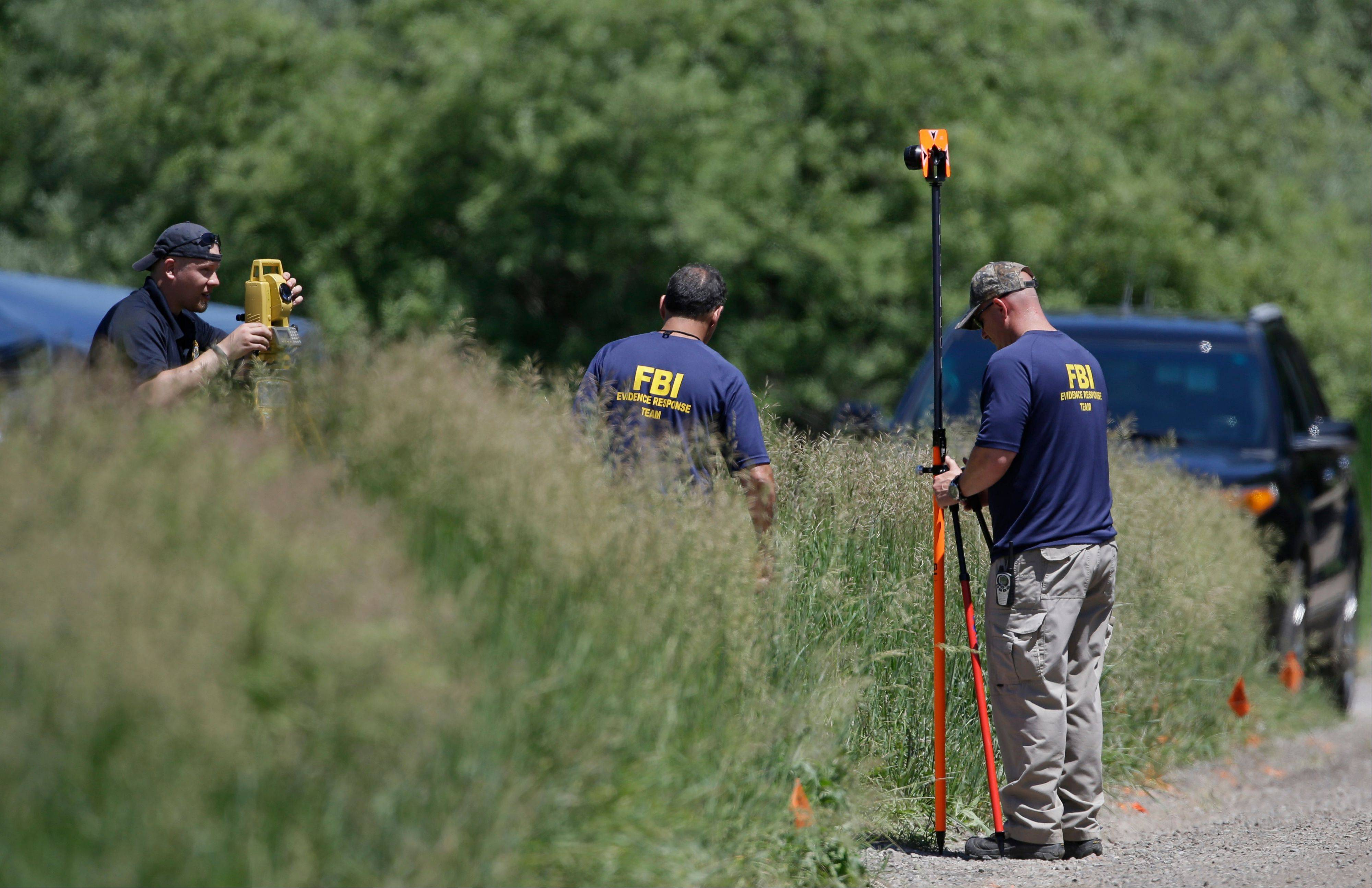Members of the FBI Evidence Response Team survey an area in Oakland Township, Mich., Monday, June 17, 2013 where officials search for the remains of Teamsters union president Jimmy Hoffa who disappeared from a Detroit-area restaurant in 1975. The search follows claims made in February by reputed Mafia captain Tony Zerilli, who told Detroit TV station WDIV that he knew where Hoffa was buried.