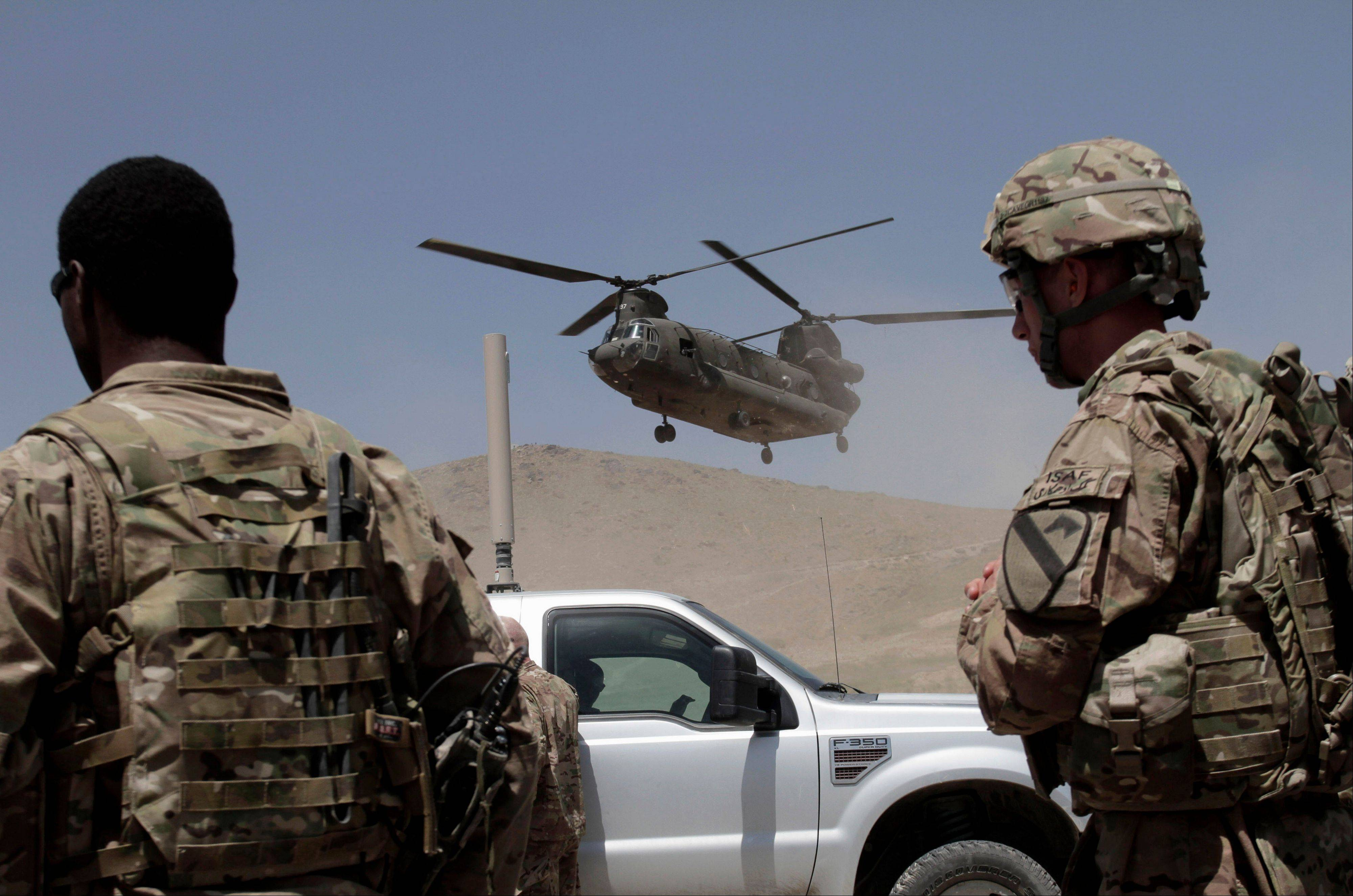 NATO solders wait for a helicopter after a ceremony at a military academy on the outskirts of Kabul, Afghanistan, Tuesday, June 18, 2013. Afghan forces have taken over the lead from the U.S.-led NATO coalition for security nationwide, Afghan President Hamid Karzai announced in the significant milestone in the 12-year war.