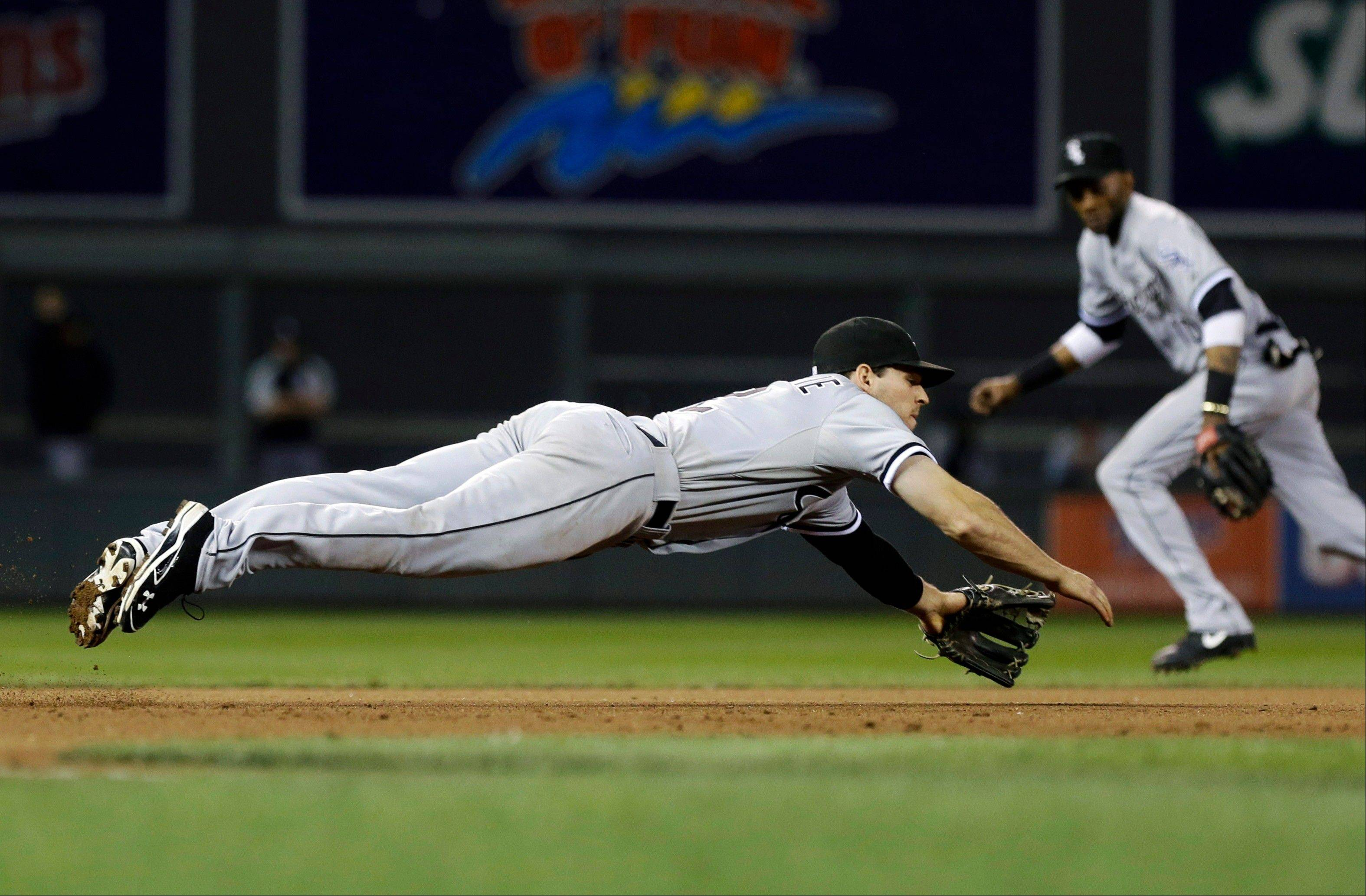 White Sox� Conor Gillaspie makes a futile dive for a sharp grounder off the bat of Minnesota Twins Ryan Doumit for a hit in the seventh inning of a baseball game Tuesday, June 18, 2013 in Minneapolis. The Twins won 7-5. (AP Photo/Jim Mone)