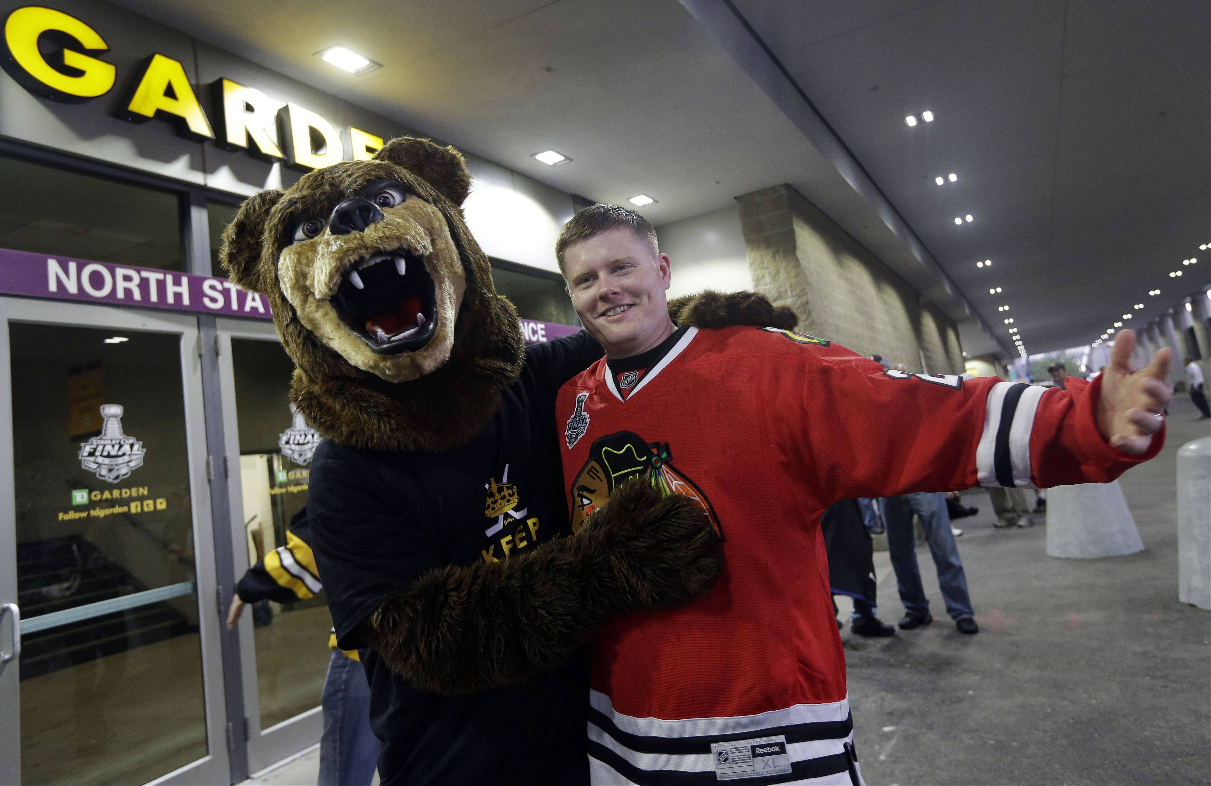 A Boston Bruins fan wearing a bear costume stands with Blackhawks fan T.J. Budka, right, of Ayer, Mass., outside the spacious TD Garden in Boston. The old Boston Garden wasn't quite so spacious or friendly for visitors.
