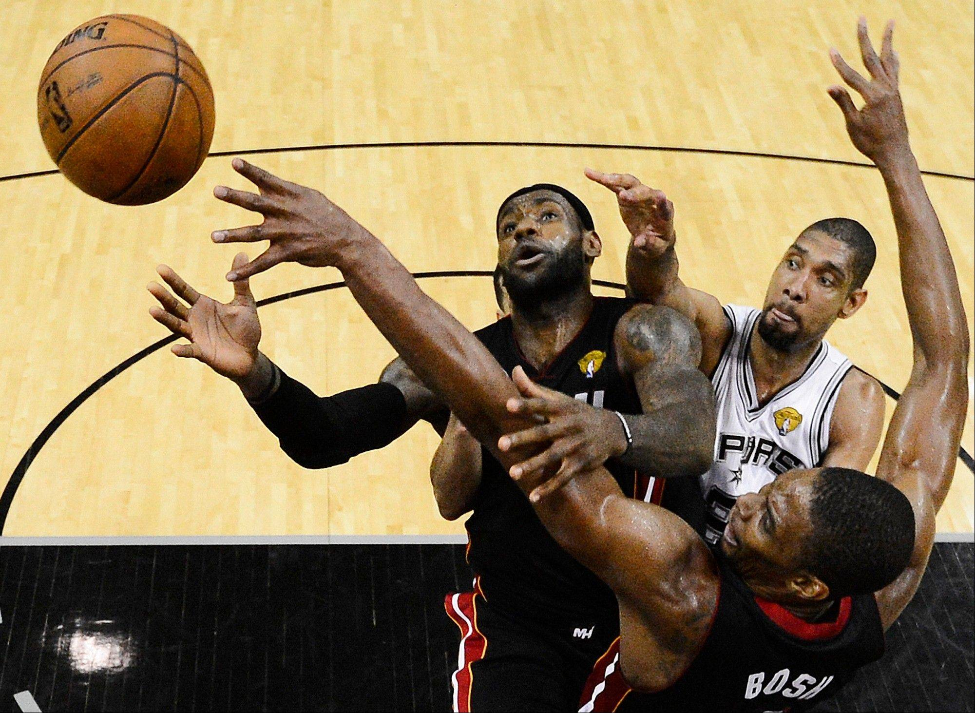 Miami Heat forward LeBron James (6), Chris Bosh (1) and the San Antonio Spurs� Tim Duncan go after a loose ball Sunday during the second half at Game 5 of the NBA Finals in San Antonio. The Spurs won 114-104.