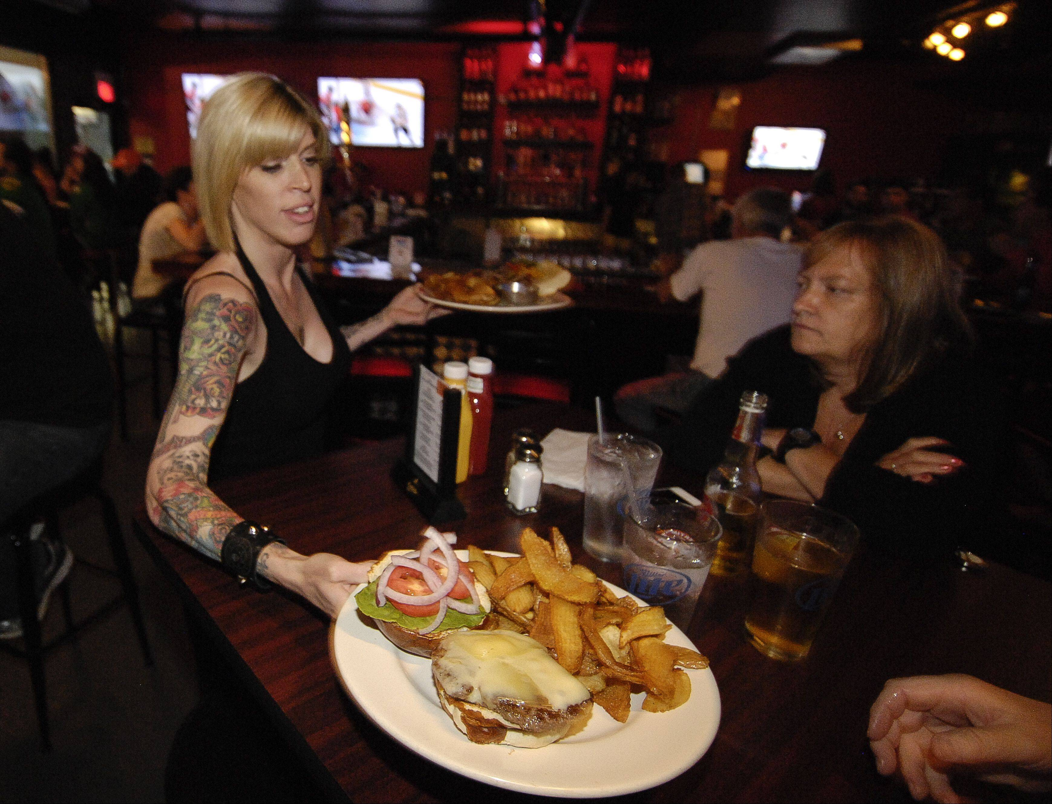Miska Pifke serves dinner to Blackhawks fans watching the game at Overtime Bar & Grill in Lombard.